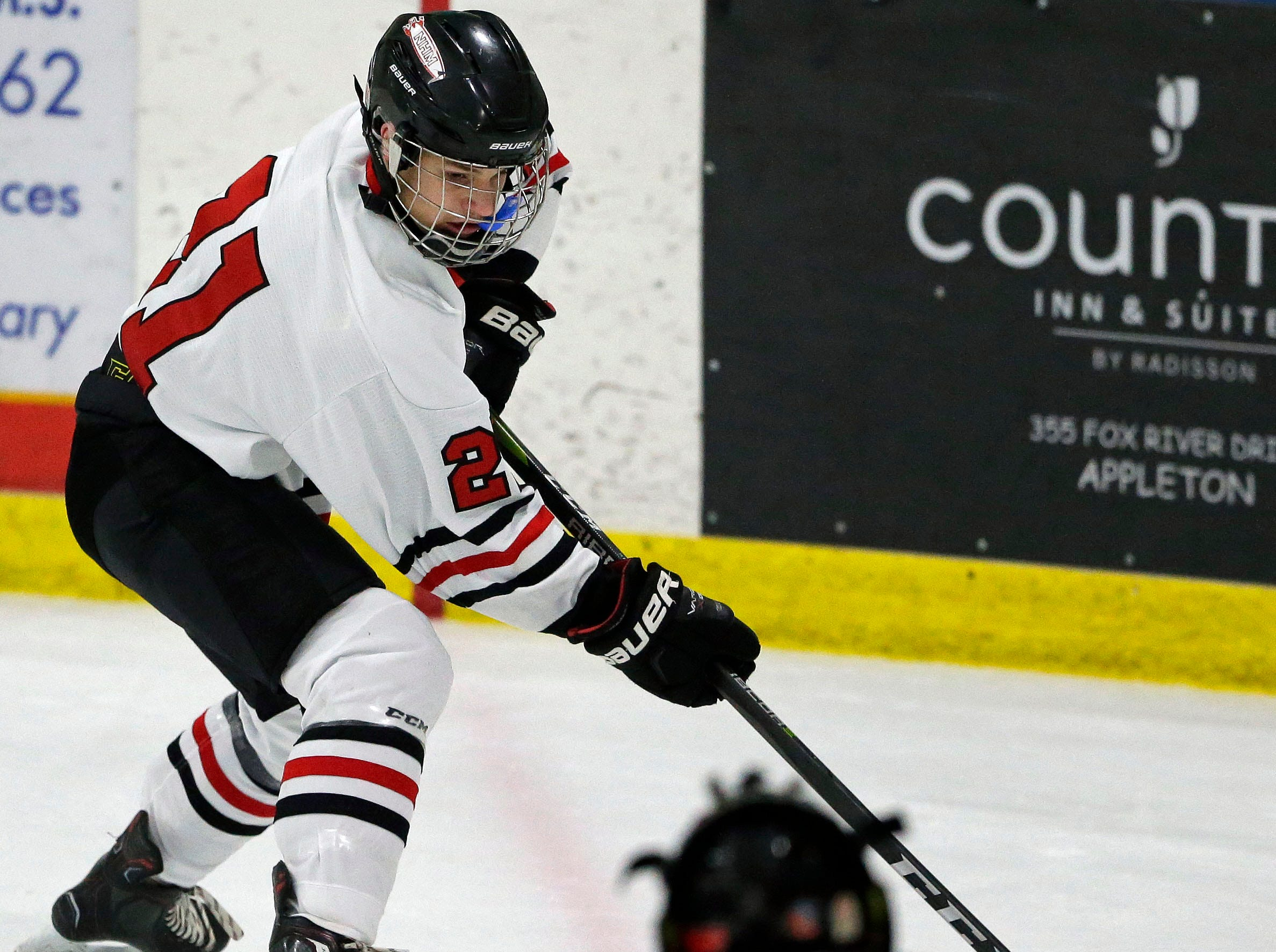 Tate Cottrell of Neenah/Hortonville/Menasha looks to pass against Oshkosh during a Badgerland Conference hockey game Tuesday, December 4, 2018, at Tri-County Ice Arena in Fox Crossing, Wis.Ron Page/USA TODAY NETWORK-Wisconsin