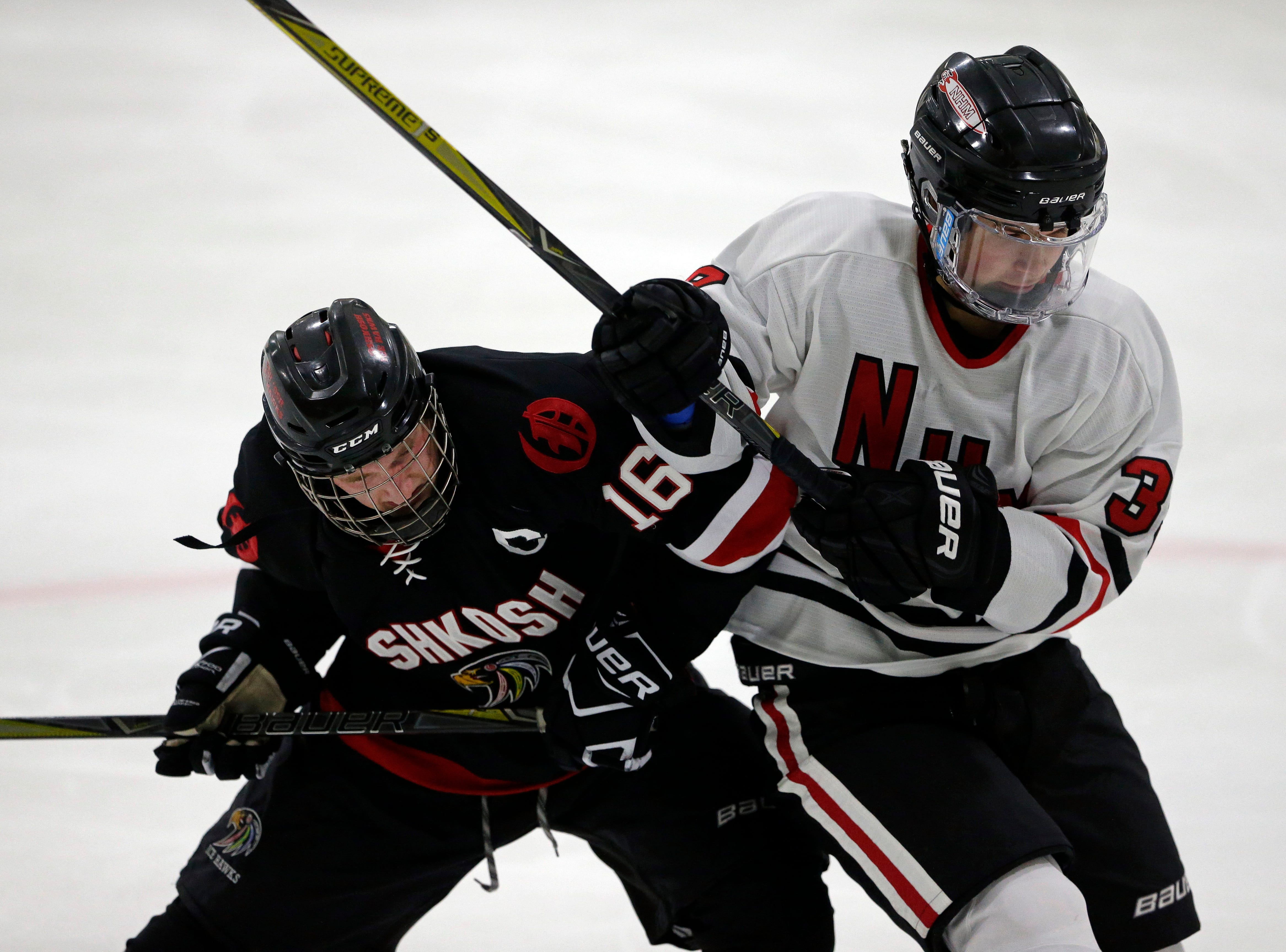 Kyle Jones of Oshkosh battles with Myles Tesky of Neenah/Hortonville/Menasha in a Badgerland Conference hockey game Tuesday, December 4, 2018, at Tri-County Ice Arena in Fox Crossing, Wis.Ron Page/USA TODAY NETWORK-Wisconsin