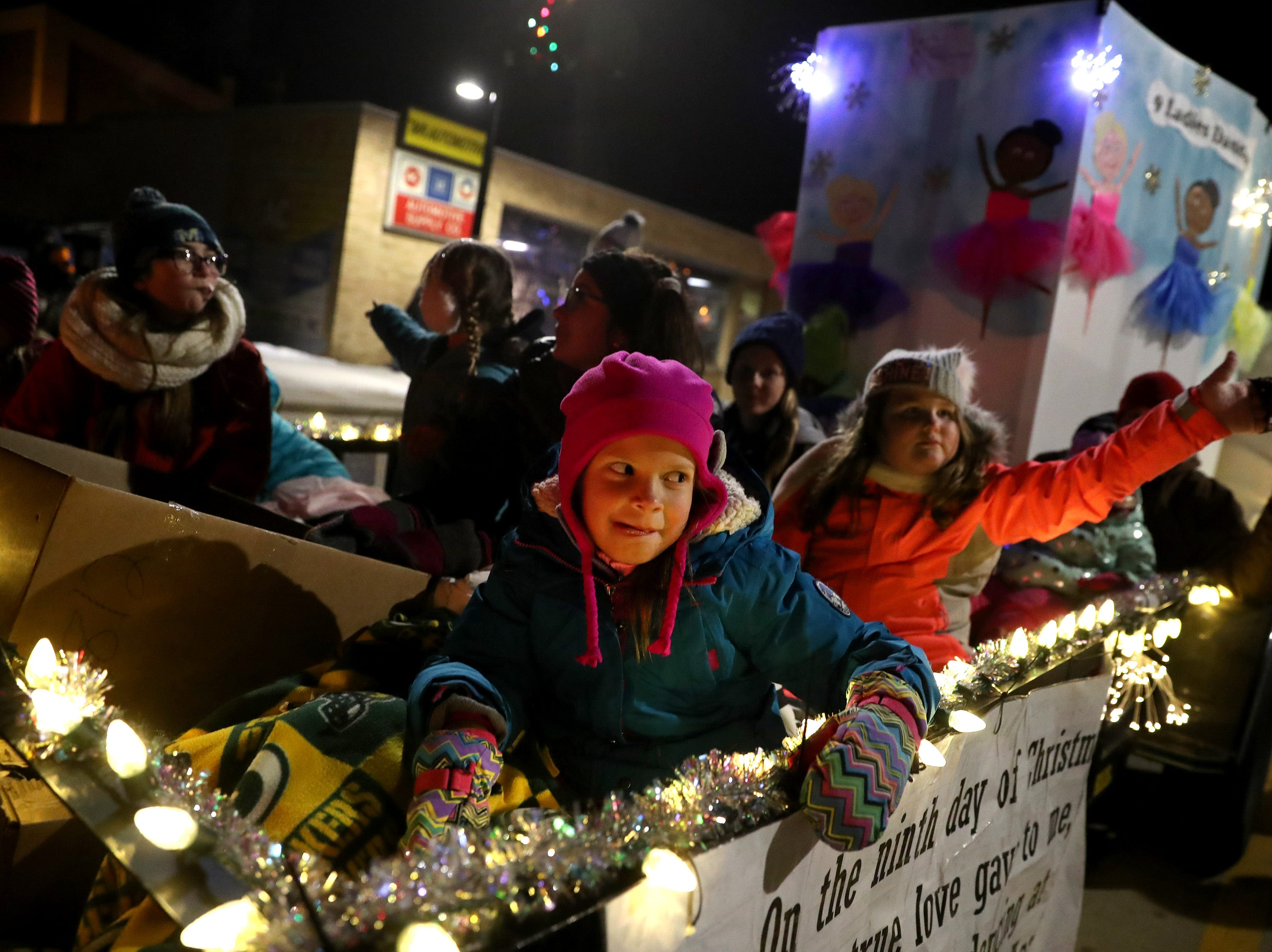 Children on the Heart of the Valley Dance Academy float wave to people along the Electric City Christmas Parade route Tuesday, Dec. 4, 2018, in Kaukauna, Wis.