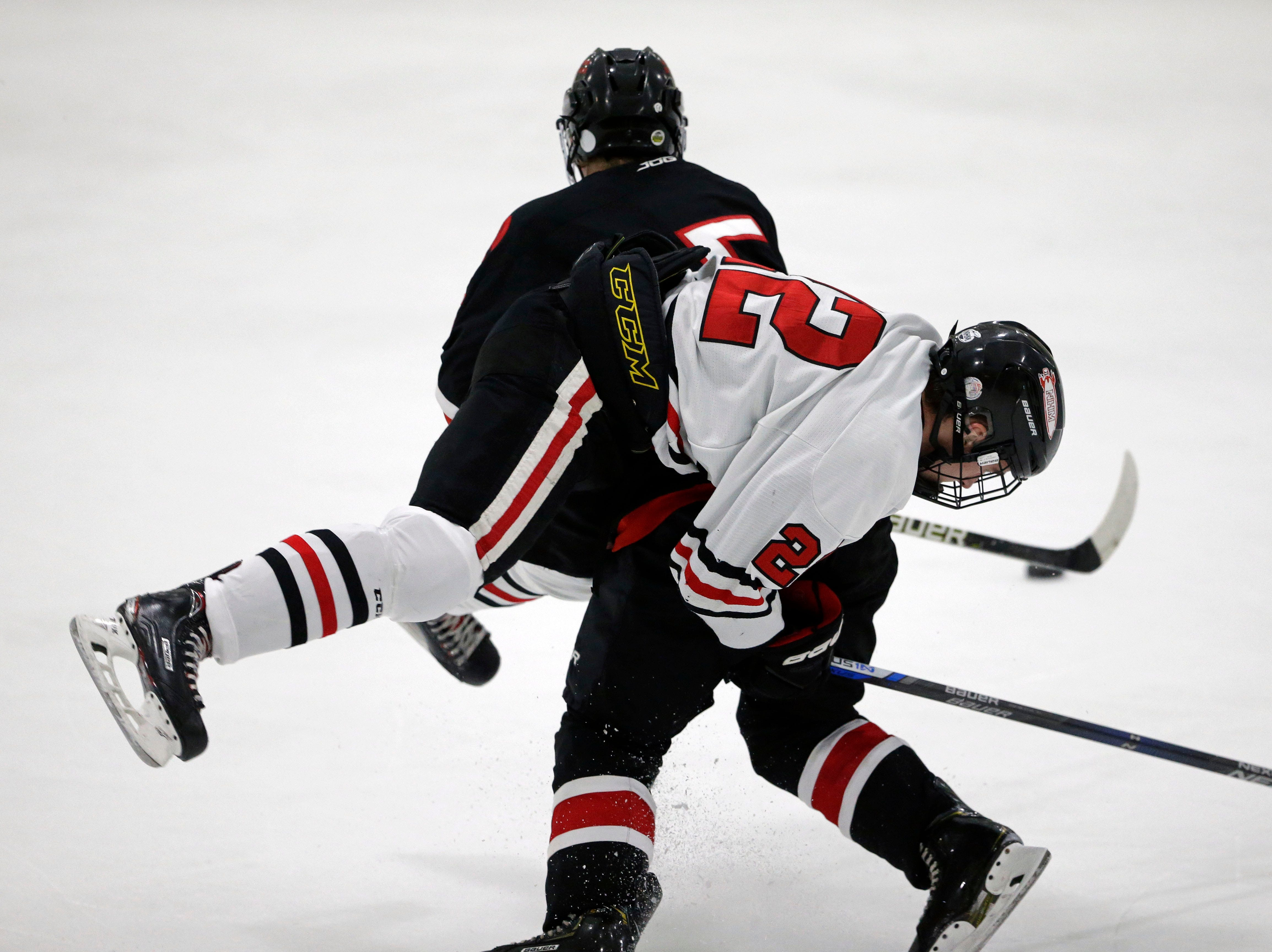 Mason Marquardt of Neenah/Hortonville/Menasha gets tangled with Andrew Grebe of Oshkosh in a Badgerland Conference hockey game Tuesday, December 4, 2018, at Tri-County Ice Arena in Fox Crossing, Wis.Ron Page/USA TODAY NETWORK-Wisconsin