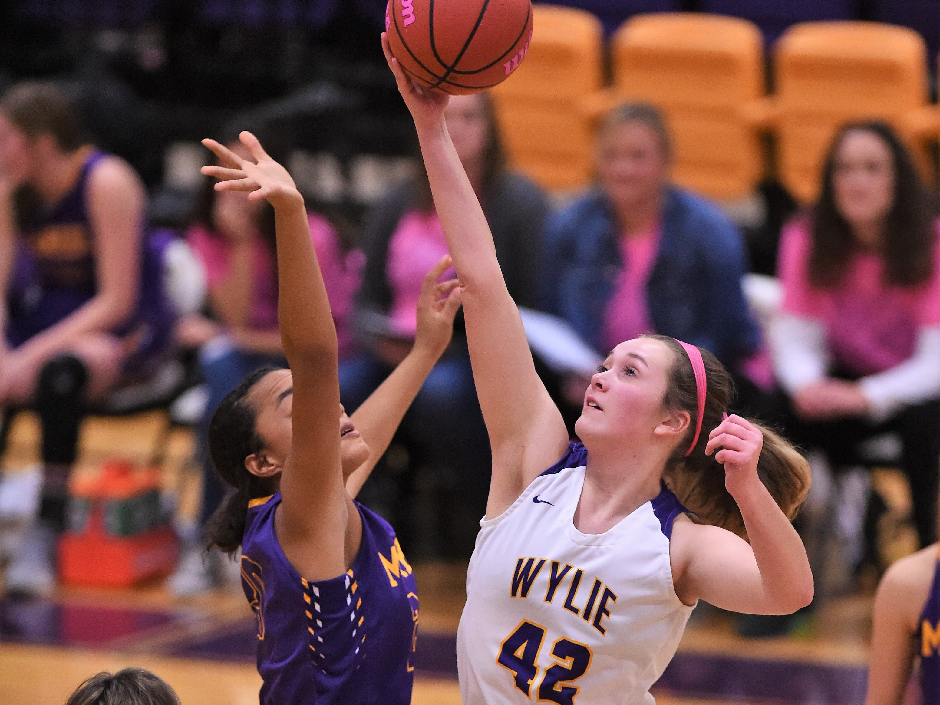 Wylie's Bailey Roberts (42) taps the opening tipoff back against Merkel in the Coaches vs. Cancer Pink Out game on Tuesday, Dec. 4, 2018. The Lady Bulldogs won 75-39.