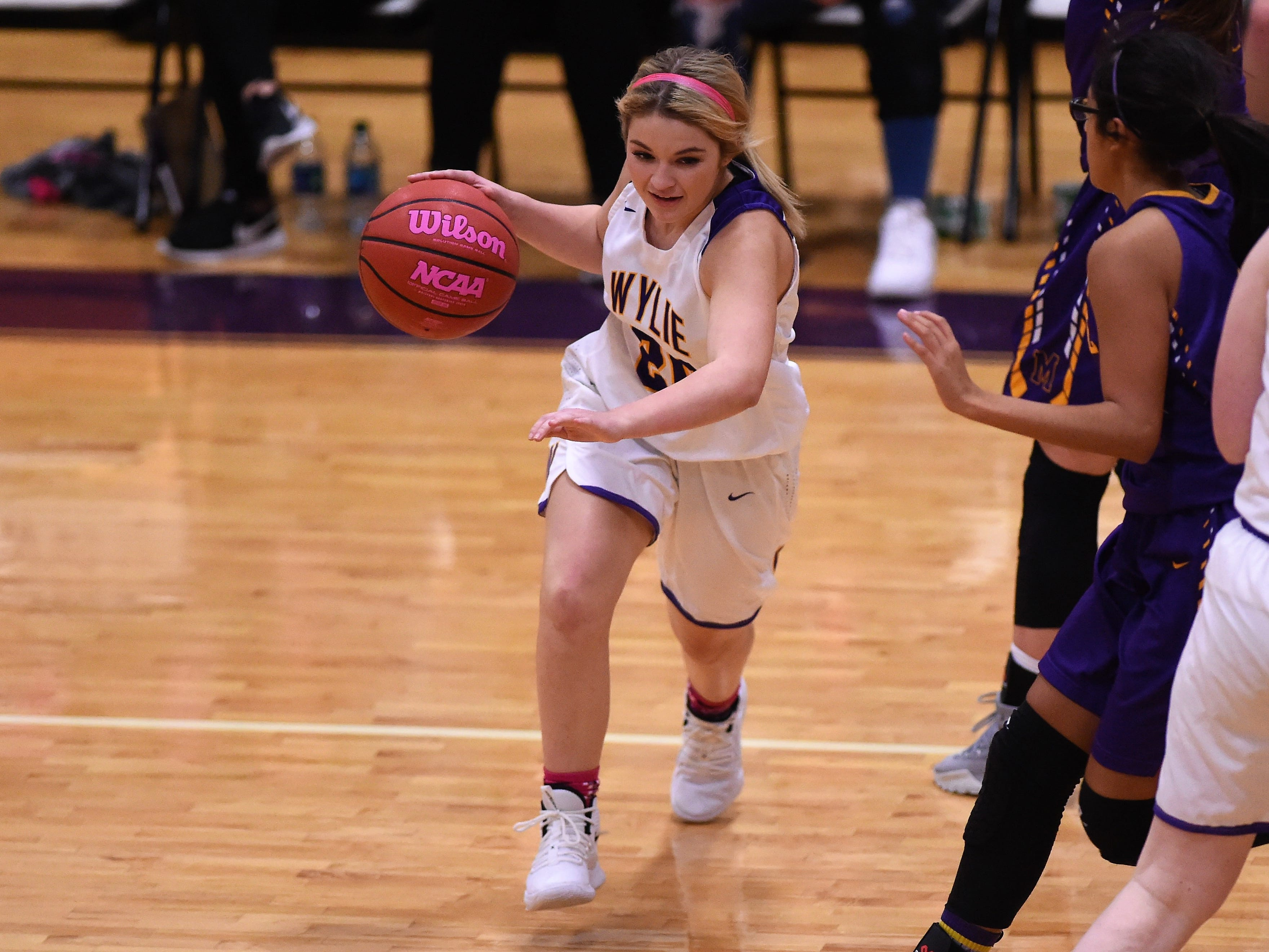 Wylie's Grace Steadman (20) goes around a Merkel defender during the Coaches vs. Cancer Pink Out game on Tuesday, Dec. 4, 2018. The Lady Bulldogs won 75-39.
