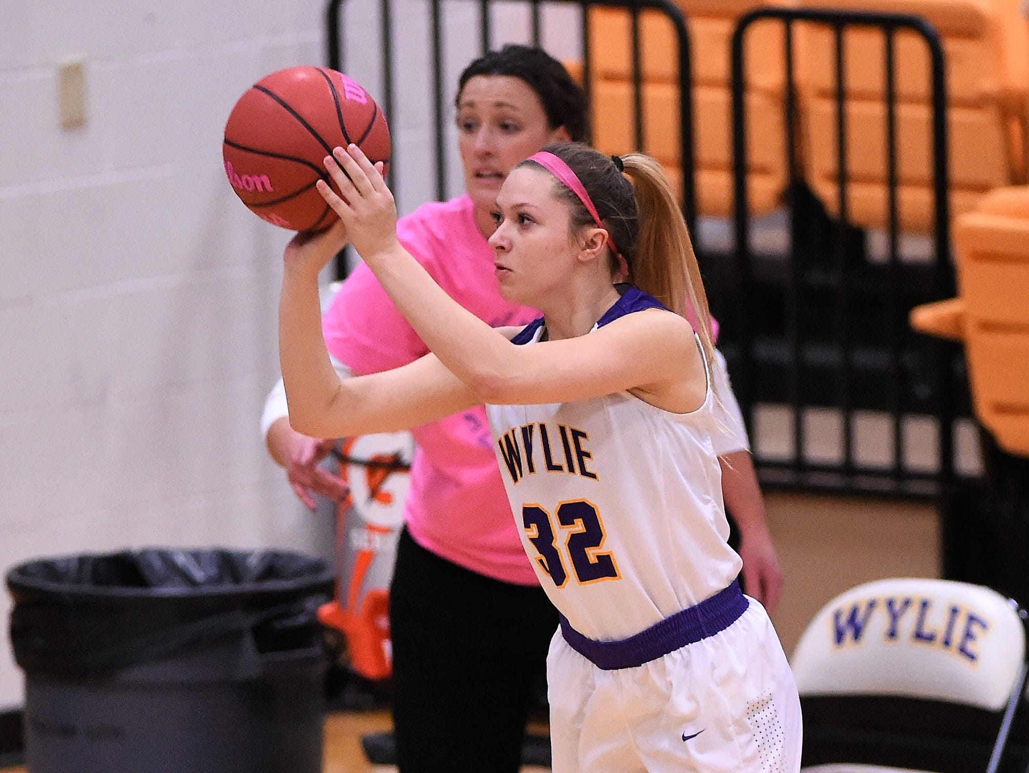 Wylie guard Skylar Williams (32) takes a 3-point shot during Tuesday night's game against Merkel.