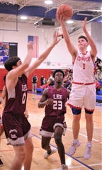 Cooper Deven Bailey (1) shoots over Midland Lee's Brian Leyva, left, as Loic Fouonji (23) looks on. Cooper beat Lee 60-57 in a nondistrict game Dec. 4 at Cougar Gym.
