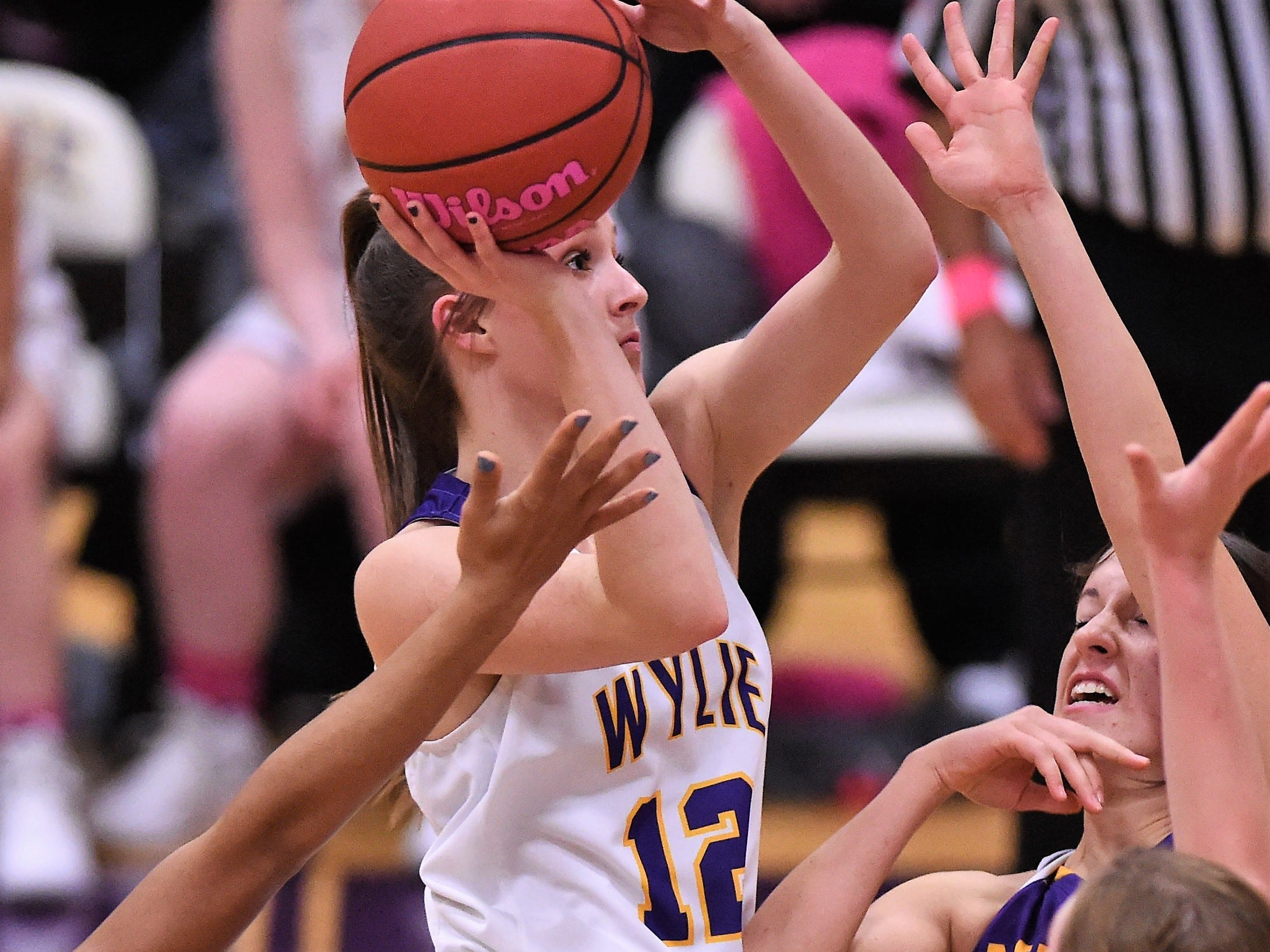 Wylie's Karis Christian (12)  goes into the air for a lay-up surrounded by Merkel defender in the Coaches vs. Cancer Pink Out game on Tuesday, Dec. 4, 2018. The Lady Bulldogs won 75-39.