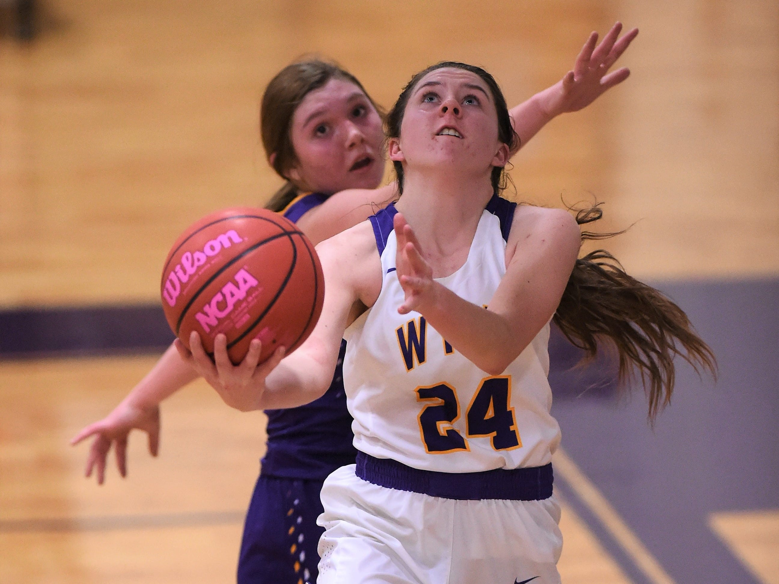 Wylie guard Mary Lovelace (24) goes under the basket against Merkel in the Coaches vs. Cancer Pink Out game on Tuesday, Dec. 4, 2018. The Lady Bulldogs won 75-39.