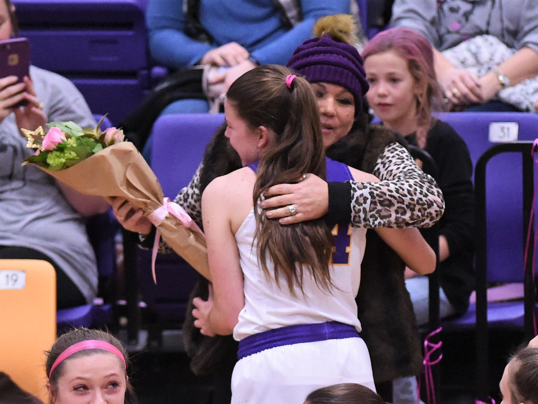 Wylie's Mary Lovelace gives Brandi Barbee a hug before the Coaches vs. Cancer Pink Out game against Merkel. The Lady Bulldogs held a bake sale and silent auction for Barbee's battle against cancer.