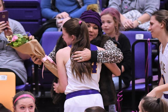Wylie's Mary Lovelace gives Brandi Barbee a hug before the Coaches vs. Cancer Pink Out game against Merkel. The Lady Bulldogs held a bake sale and silent auction to assist in Barbee's battle against cancer.