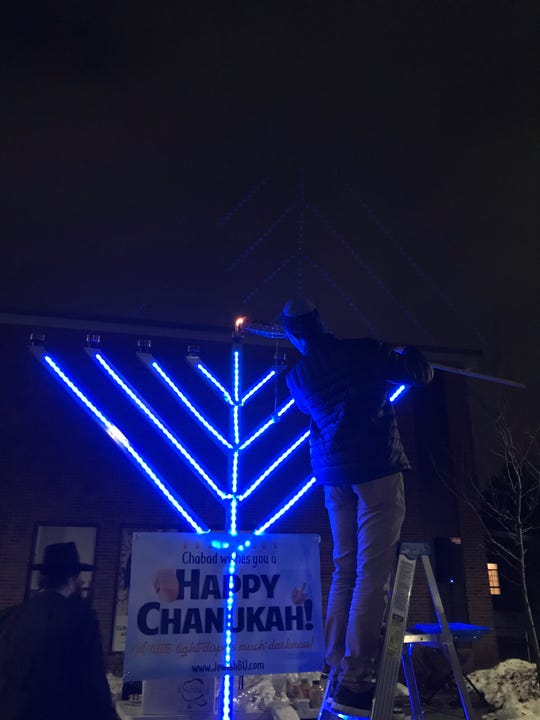 Ori Karudo, the executive board president of Chabad at Binghamton University, lights a menorah at Binghamton University on Dec. 9.