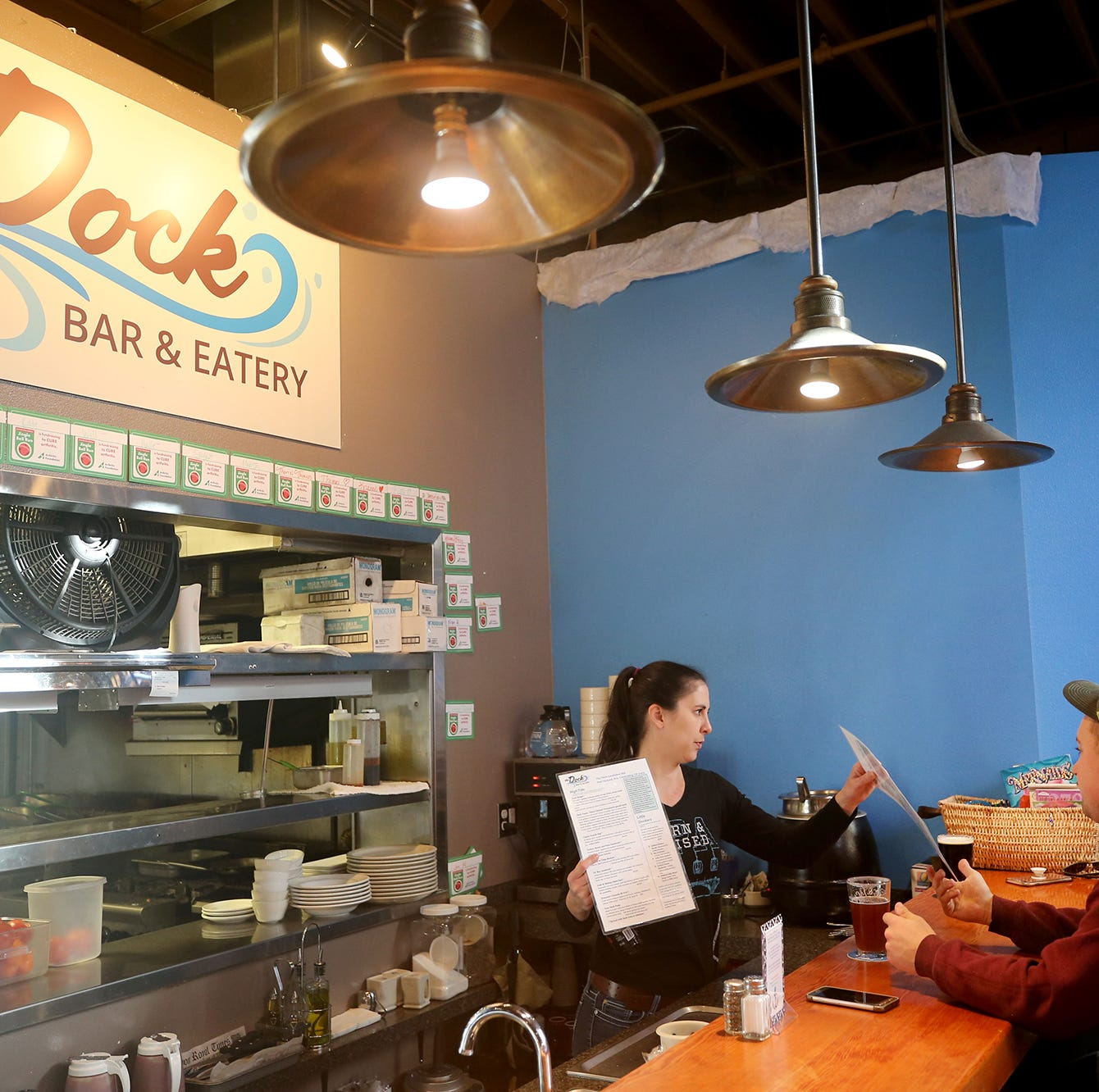 Manager Kate Huck takes the menus after customer orders at The Dock Bar & Eatery in the Port Orchard Market.