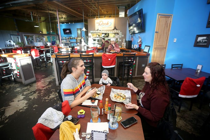 Customers Rebekah Johnson of Port Orchard her son Roland Erickson, 7 months, and Magan Freeman of Bangor eat at The Dock Bar & Eatery in the Port Orchard Market. Features fresh cod tacos.