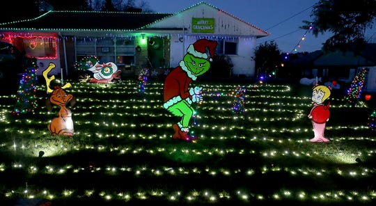 The Grinch takes a strand of lights from the lawn of a Sunrise Drive home in Bremerton.
