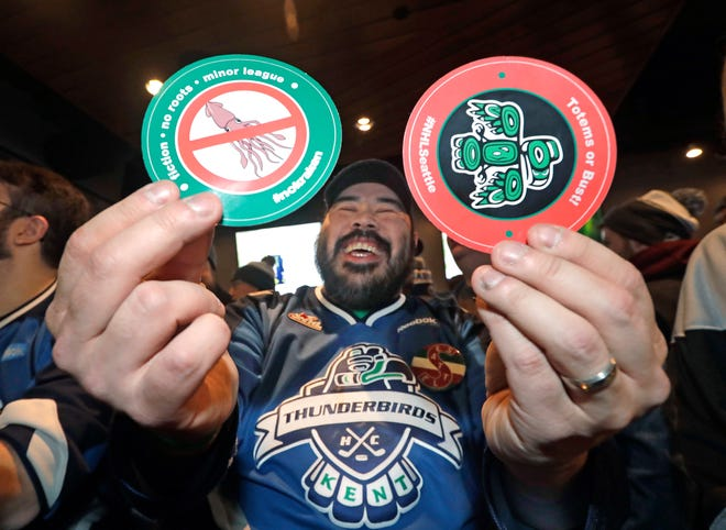 Otto Rogers playfully holds up stickers against the proposed name Kraken and in support of Totems following the announcement of a new NHL hockey team in Seattle, at a celebratory party Tuesday, Dec. 4, 2018, in Seattle.
