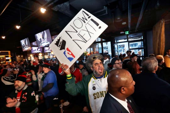 "Kris ""Sonic Guy"" Brannon holds up a sign in support of adding an NBA team following the announcement of a new NHL hockey team in Seattle, at a celebratory party Tuesday, Dec. 4."