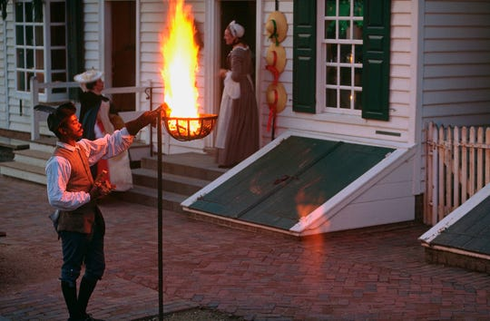 Preston Jones fuels the fire of a cresset at the James Geddy House.