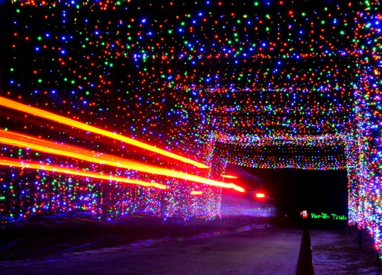 A car passes through a tunnel of Christmas lights at the Space Coast LIghtfest at Wickham Park.