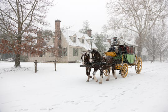 Dan Hard drives the Carter Coach in the falling snow in Colonial Williamsburg.