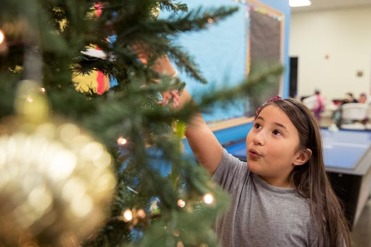 Raelynn Trejo, 8, checks out the Christmas tree at the Boys & Girls Club of Alice on Tuesday, December 4, 2018.