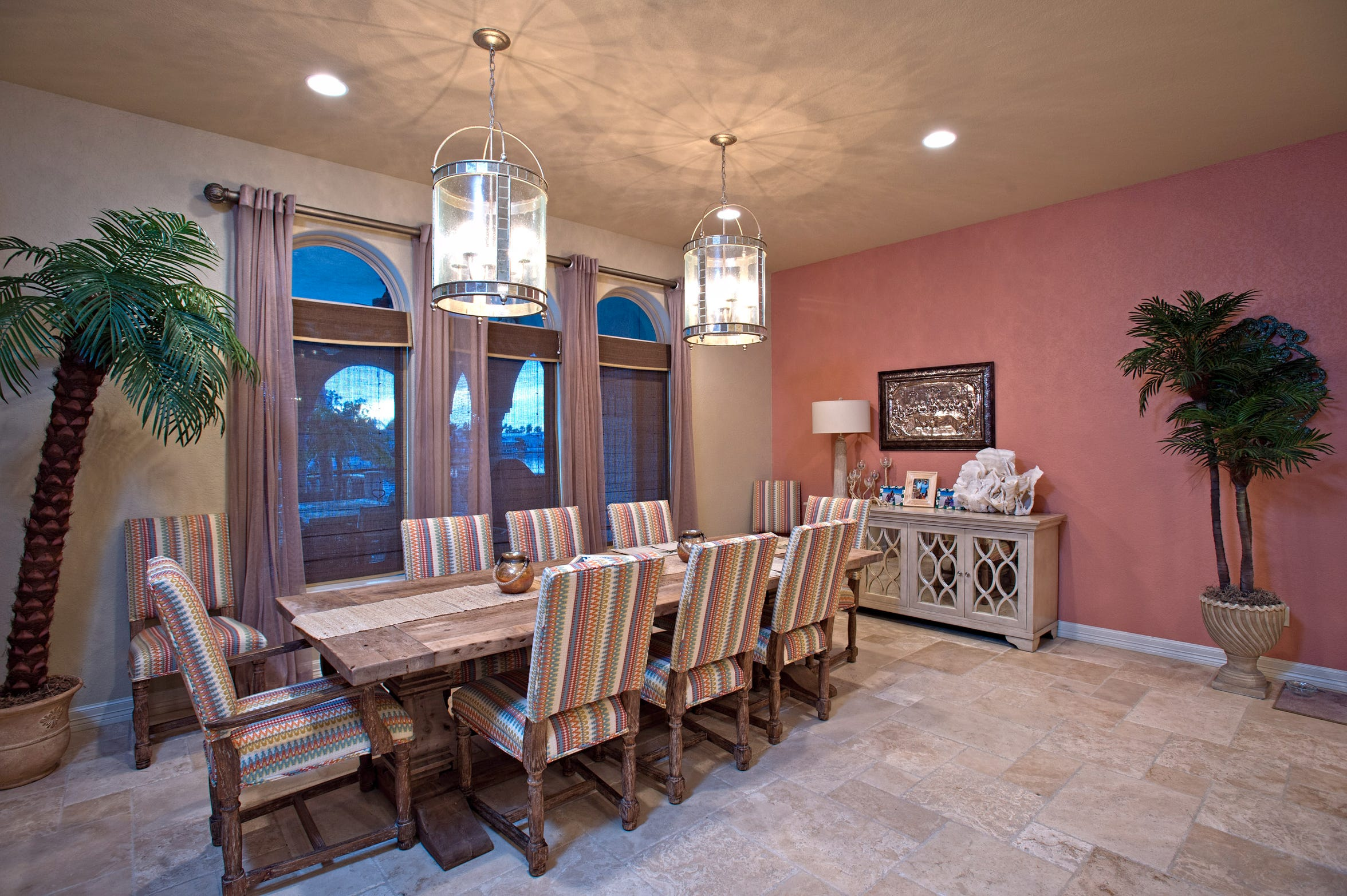 The open dining space adjacent to the kitchen overlooks the water via three large arch topped windows.