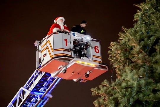 Santa gets ready to put the star on the tree in Glassboro .