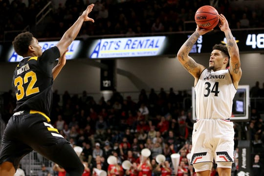 Cincinnati Bearcats guard Jarron Cumberland (34) rises for a 3-pointer as Northern Kentucky Norse forward Dantez Walton (32) defends in the second half of an NCAA college basketball game, Tuesday, Dec. 4, 2018, at Fifth Third Arena in Cincinnati.