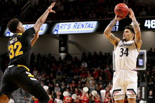 Cincinnati Bearcats guard Jarron Cumberland (34) rises for a 3-pointer as Northern Kentucky Norse forward Dantez Walton (32) defends in the second half of an NCAA college basketball game, Tuesday, Dec. 4, 2018, at Fifth Third Arena in Cincinnati.