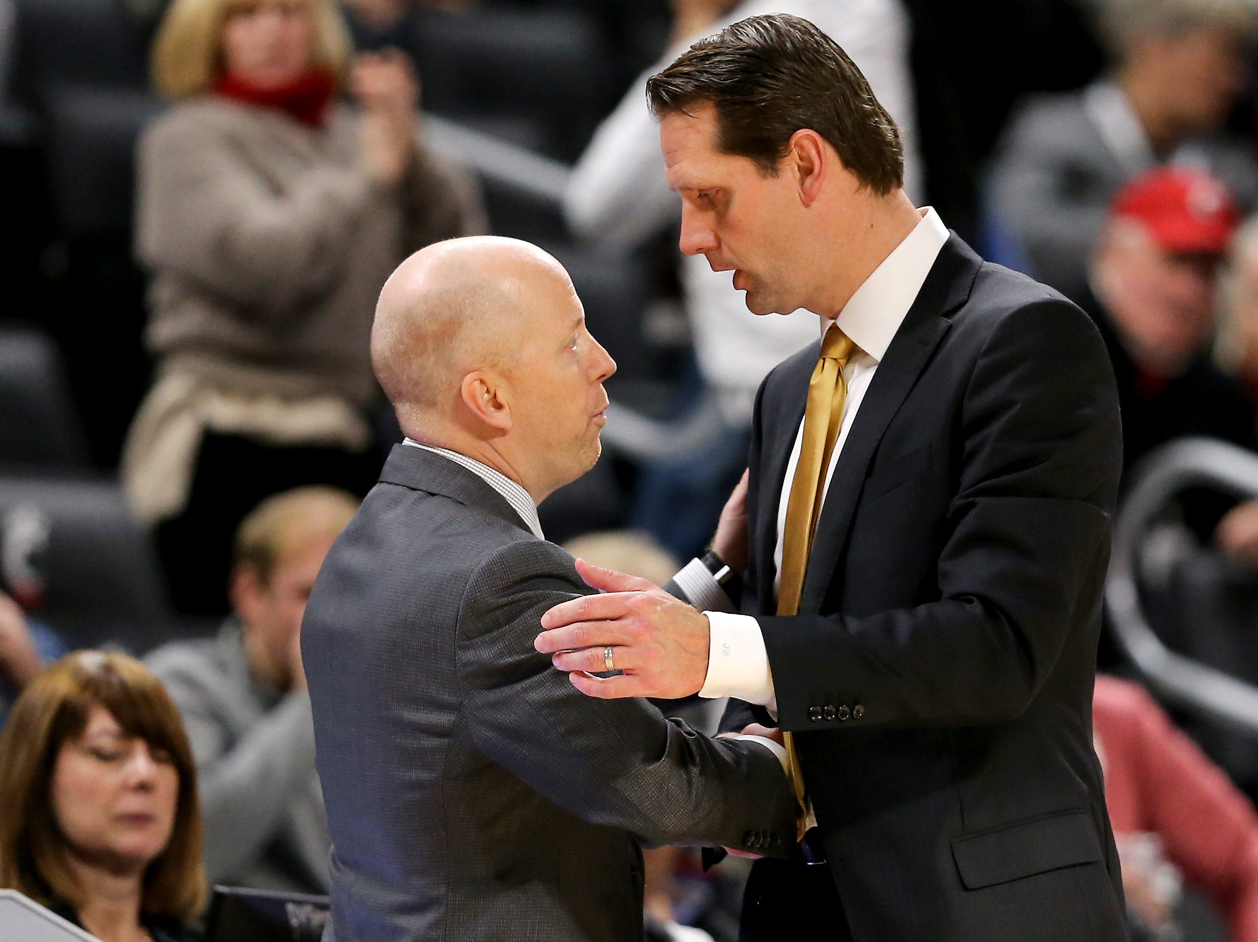 Cincinnati Bearcats head coach Mick Cronin, left, and Northern Kentucky Norse head coach John Brannen, shake hands in the final seconds of the second half of an NCAA college basketball game, Tuesday, Dec. 4, 2018, at Fifth Third Arena in Cincinnati.