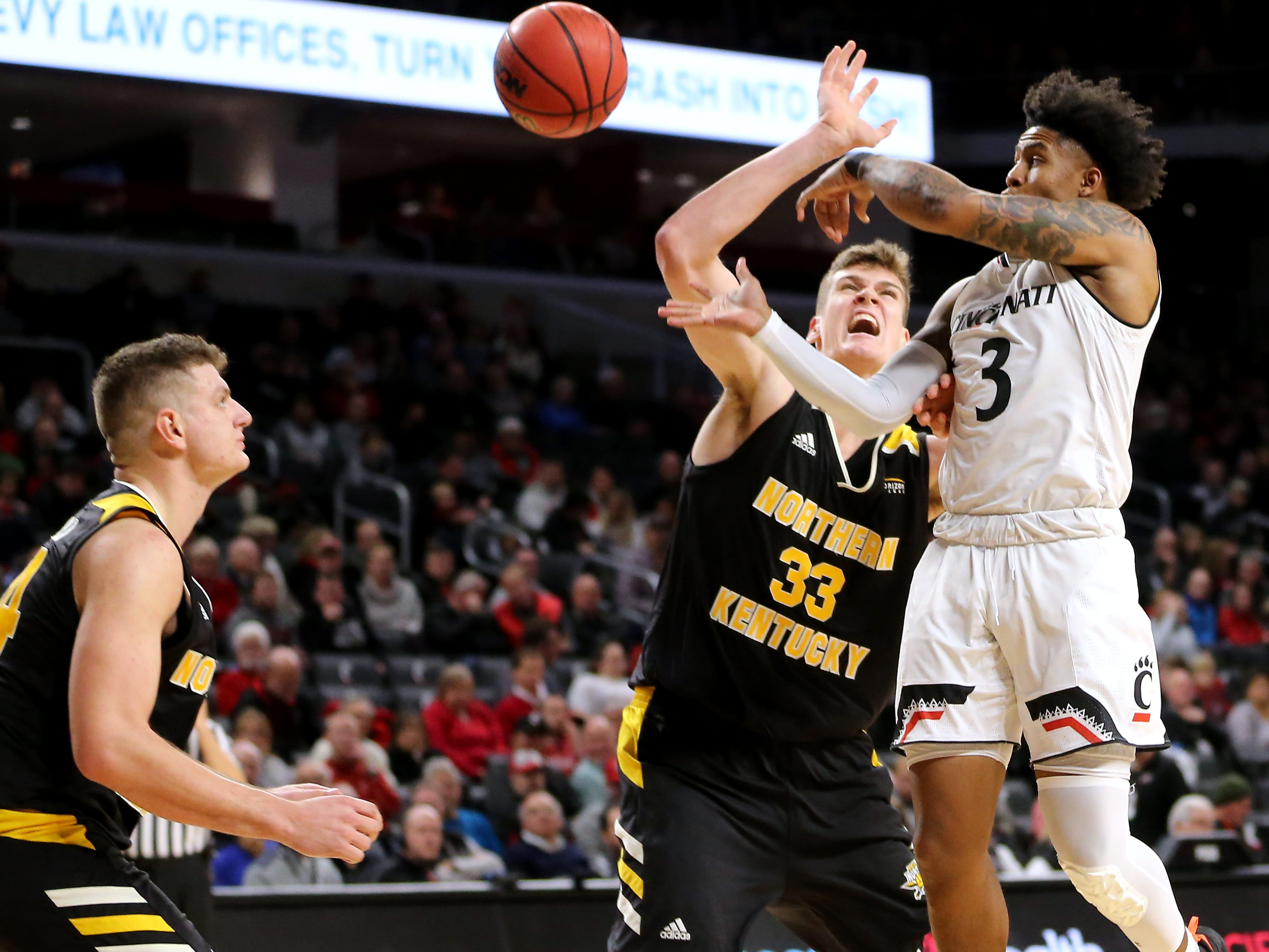 Cincinnati Bearcats guard Justin Jenifer (3) passes the ball out of the paint as Northern Kentucky Norse center Chris Vogt (33) defends in the second half of an NCAA college basketball game, Tuesday, Dec. 4, 2018, at Fifth Third Arena in Cincinnati.