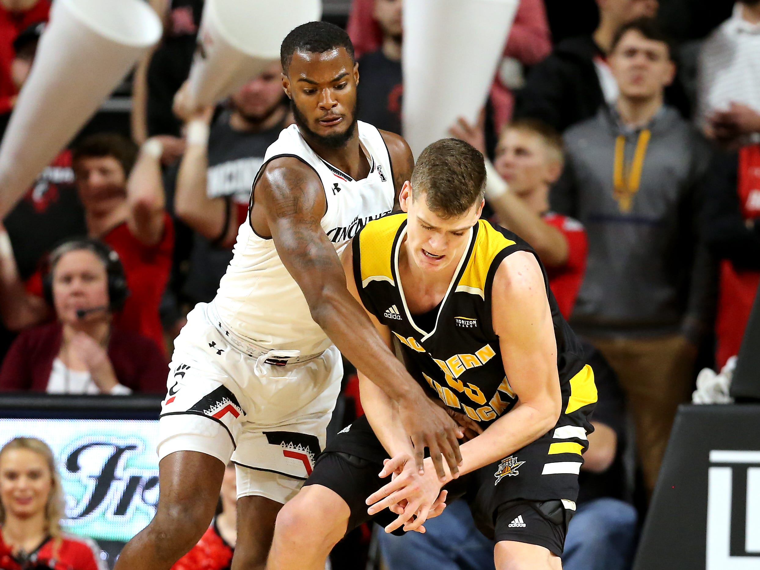 Cincinnati Bearcats guard Trevor Moore (5) chases a loose ball from Northern Kentucky Norse center Chris Vogt (33) in the first half of an NCAA college basketball game, Tuesday, Dec. 4, 2018, at Fifth Third Arena in Cincinnati.