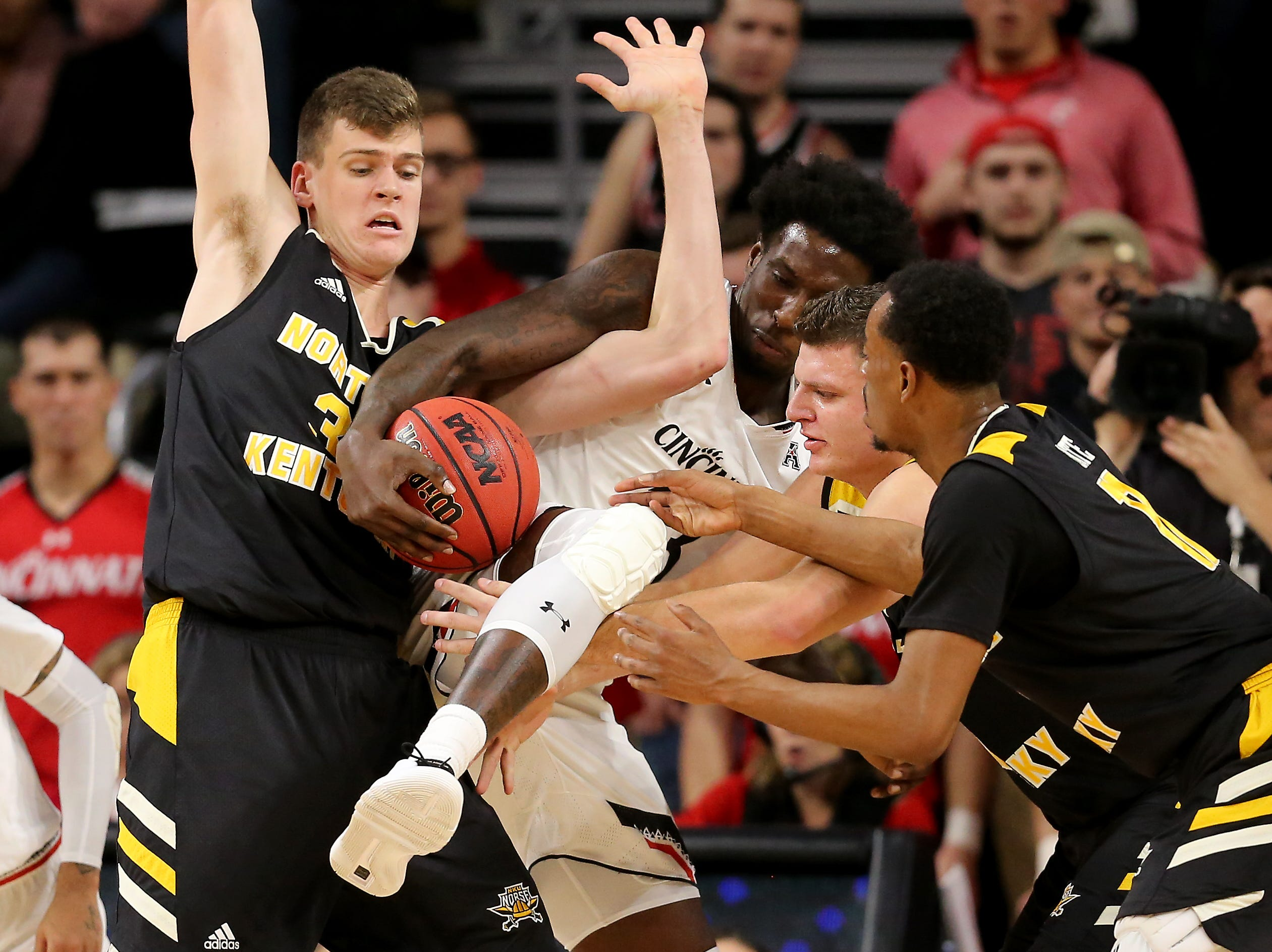 Cincinnati Bearcats center Nysier Brooks (33), center, brings in a loose ball as Northern Kentucky Norse center Chris Vogt (33) and Northern Kentucky Norse forward Drew McDonald (34) defend in the first half of an NCAA college basketball, Tuesday, Dec. 4, 2018, at Fifth Third Arena in Cincinnati.
