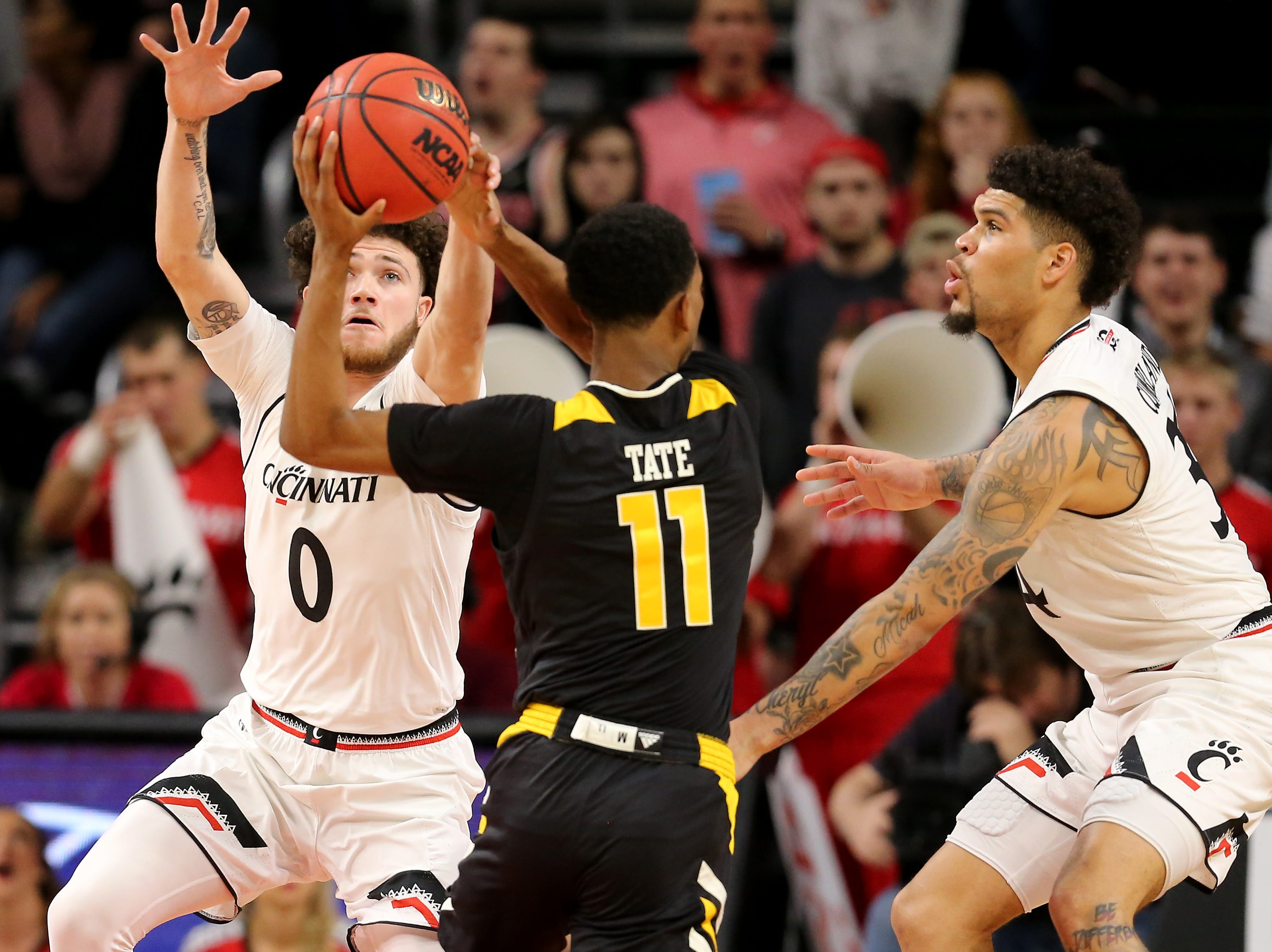 Cincinnati Bearcats guard Logan Johnson (0) eyes the basketball as Northern Kentucky Norse guard Jalen Tate (11) looks to pass in the second half of an NCAA college basketball game, Tuesday, Dec. 4, 2018, at Fifth Third Arena in Cincinnati.