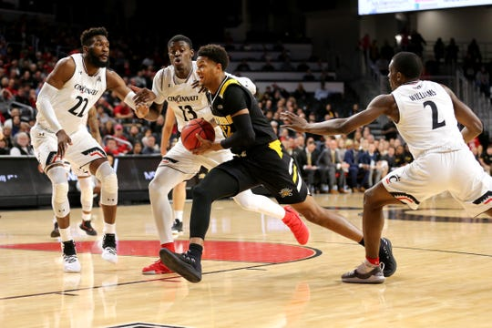 Northern Kentucky Norse forward Dantez Walton (32) drives to the basket as Cincinnati Bearcats forward Eliel Nsoseme (22) and Cincinnati Bearcats forward Tre Scott (13) defends in the first half of an NCAA college basketball game, Tuesday, Dec. 4, 2018, at Fifth Third Arena in Cincinnati.
