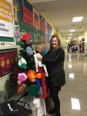 Principal Cathy Kobylarlz o f Stony Brook Elementary School in North Plainfield hangs Fun Fur scarves as garlands on the school's mitten tree for students in need.