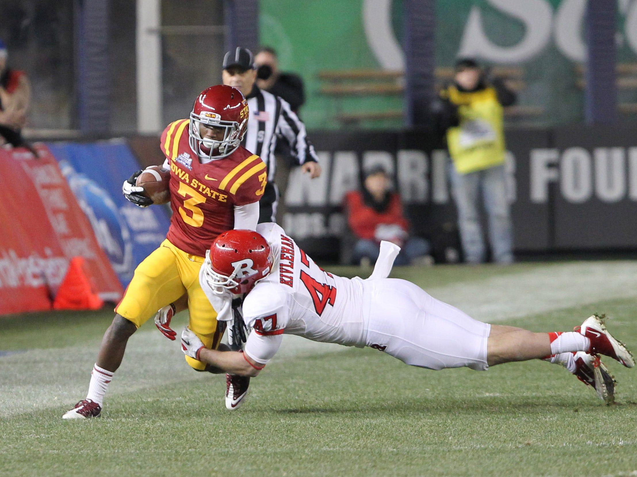 Iowa State Cyclones wide receiver Aaron Horne (3) carries the ball as Rutgers Scarlet Knights defensive back Patrick Kivlehan (47) comes in for the tackle during the third quarter of the 2011 Pinstripe Bowl at Yankee Stadium. Rutgers won 27-13.