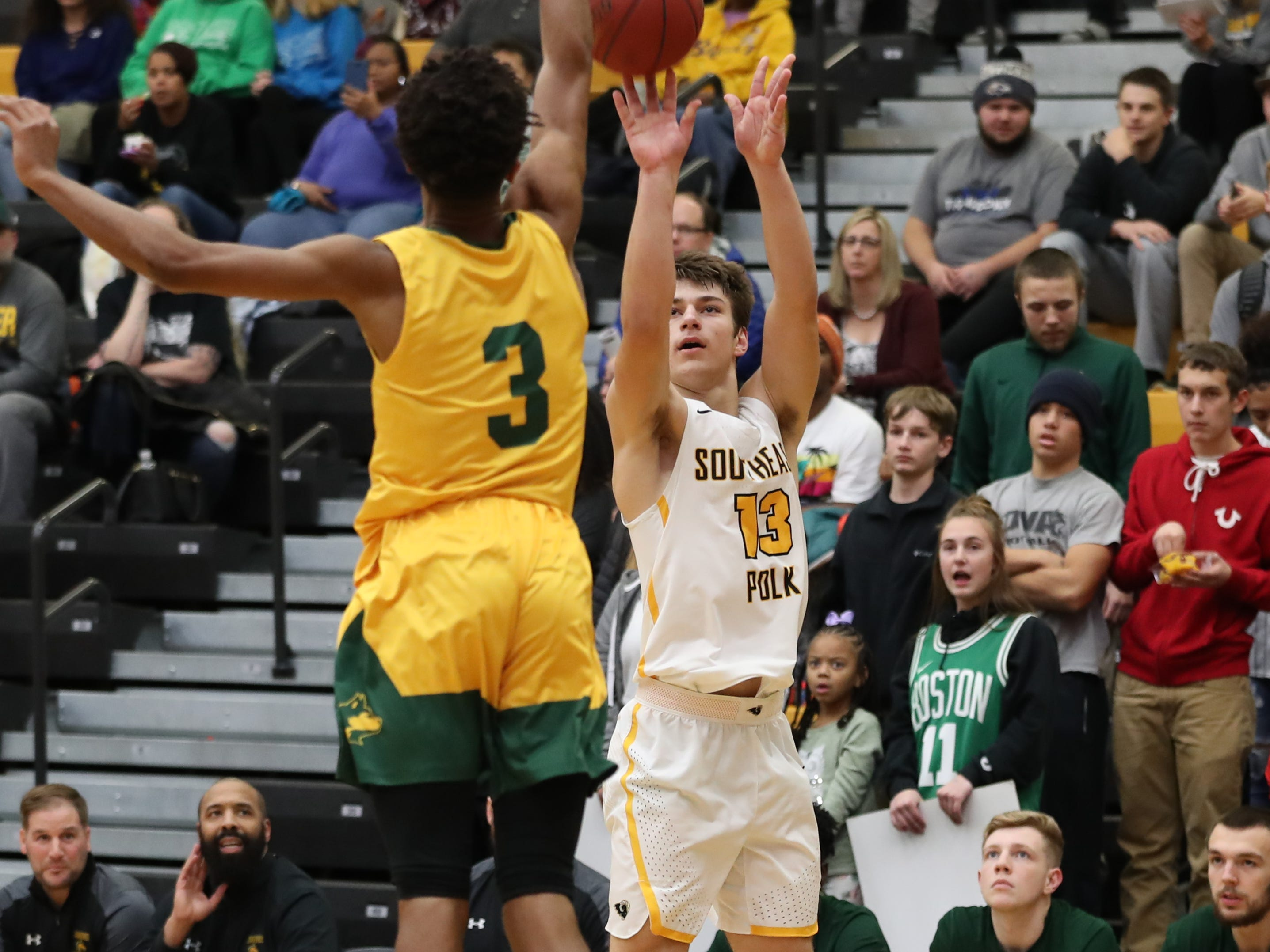 Southeast Polk Rams Dominic Caggiano (13) shoots over the hand of Hoover Huskies Hosea Treadwell (3) at Southeast Polk High School.