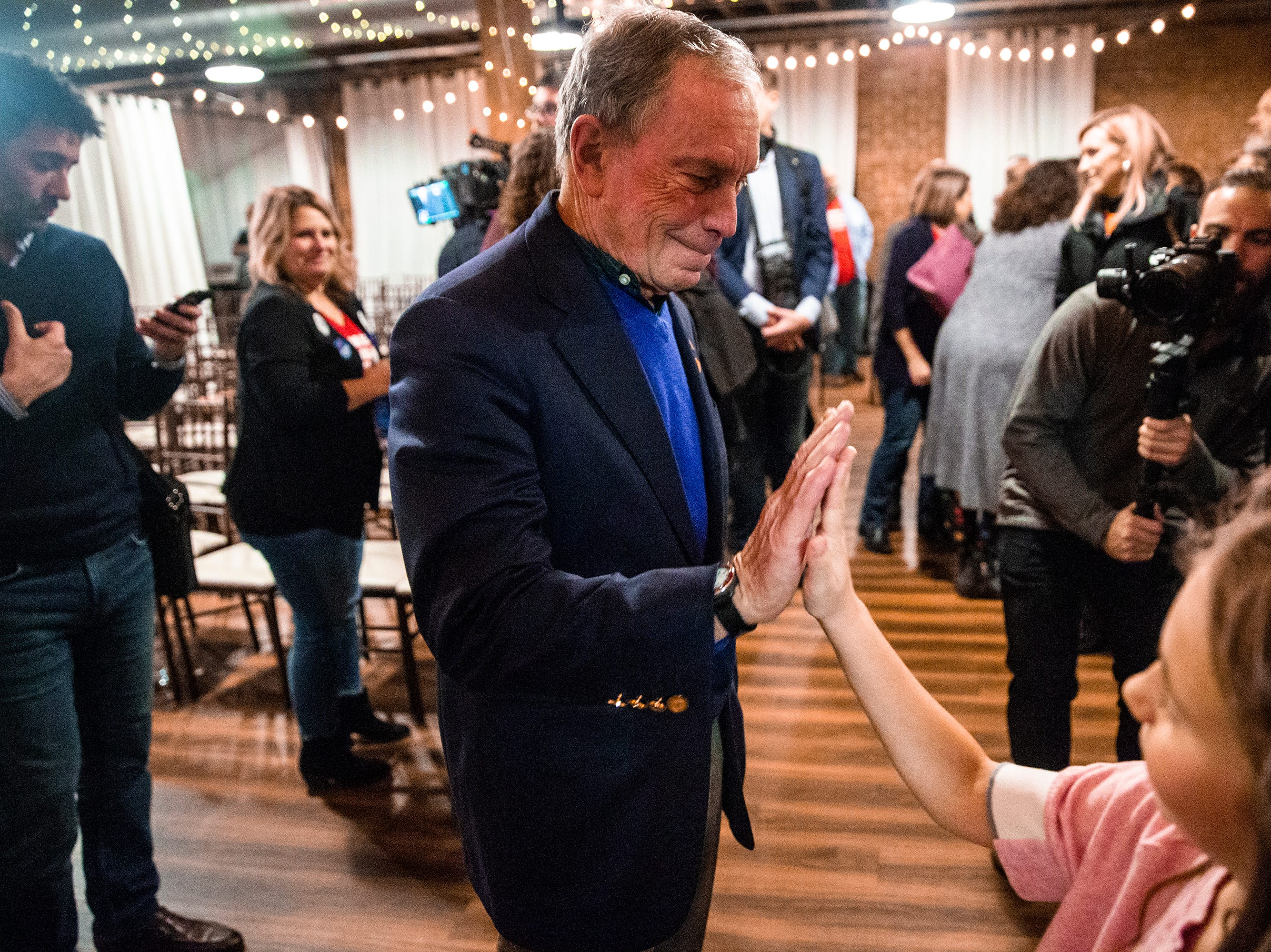 Former New York City Mayor Michael Bloomberg gives a high-five to a young girl at the Iowa Moms Demand Action member meeting he was visiting on Tuesday, Dec. 4, 2018, at the Iowa Taproom in Des Moines.