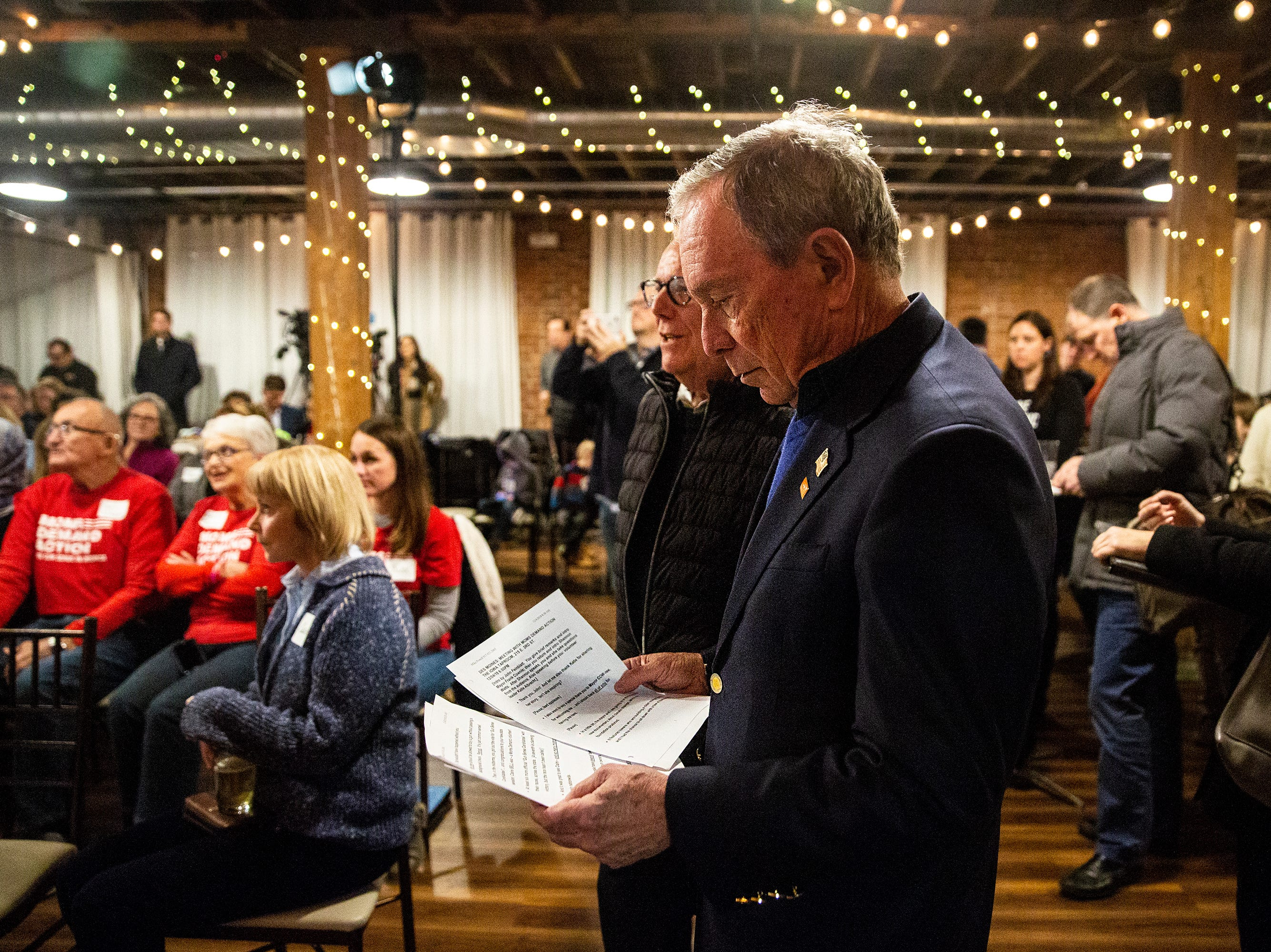 Former New York City Mayor Michael Bloomberg looks at his notes before speaking to the crowd gathered at an Iowa Moms Demand Action member meeting on Tuesday, Dec. 4, 2018, at the Iowa Taproom in Des Moines.