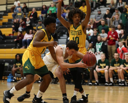 Southeast Polk Rams Daniel Hackbarth (10) is defended by Hoover Huskies Kenny Quinn (1) and Hoover Huskies Manny Austin (10) at Southeast Polk High School.