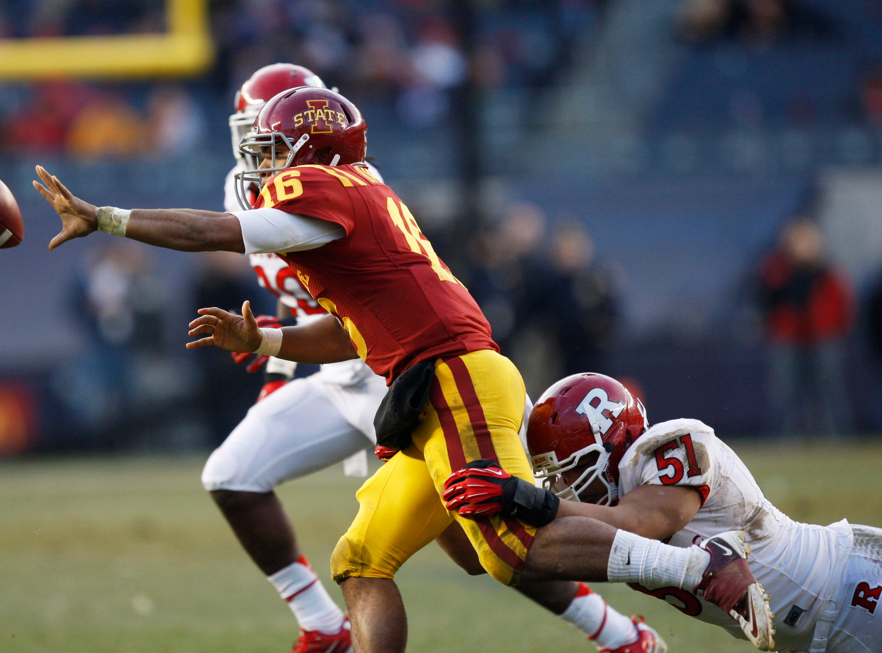 Iowa State Cyclones quarterback Jared Barnett (16) passes the ball while being tackled by Rutgers Scarlet Knights player Manny Abreu (51) during the Pinstripe Bowl at Yankee Stadium. Mandatory Credit: Frances Micklow/The Star-Ledger via USA TODAY Sports