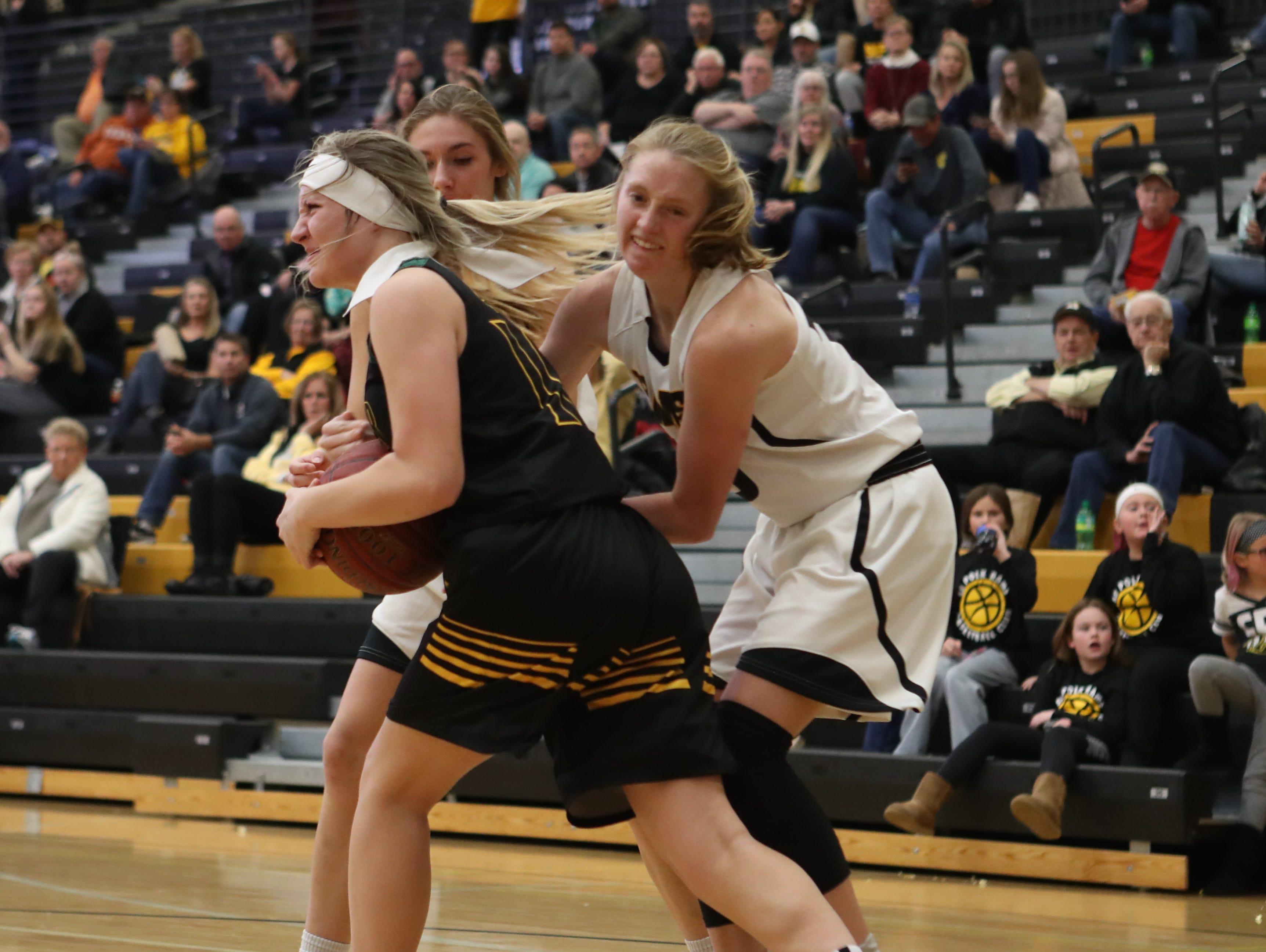 Hoover Huskies Rachel Math (4) and Southeast Polk Rams Grace Larkins (10) battle for a rebound at Southeast Polk High School.