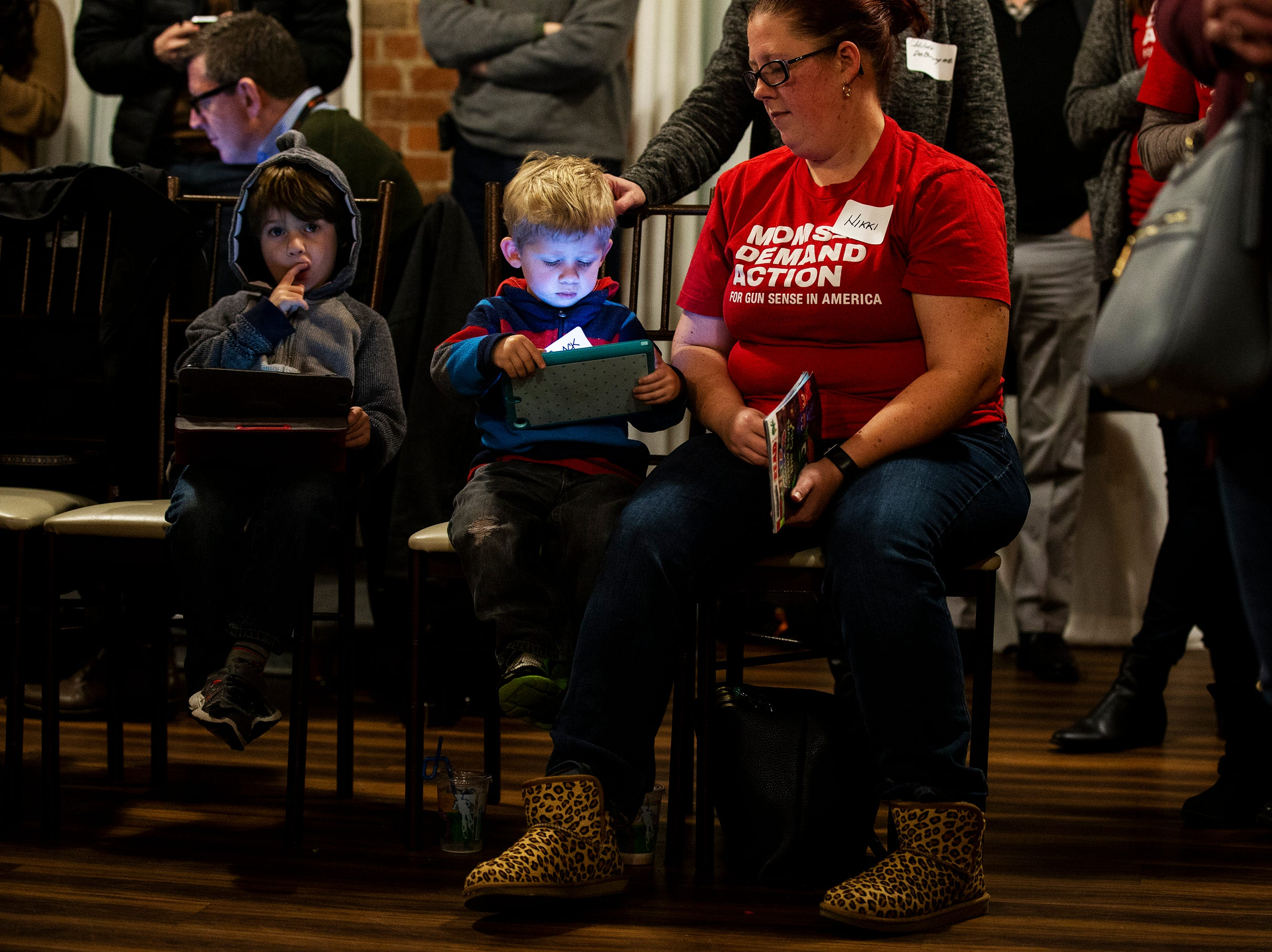 A pair of boys look down at tablets while Former New York City Mayor Michael Bloomberg speaks at the Iowa Moms Demand Action member meeting on Tuesday, Dec. 4, 2018, at the Iowa Taproom in Des Moines.