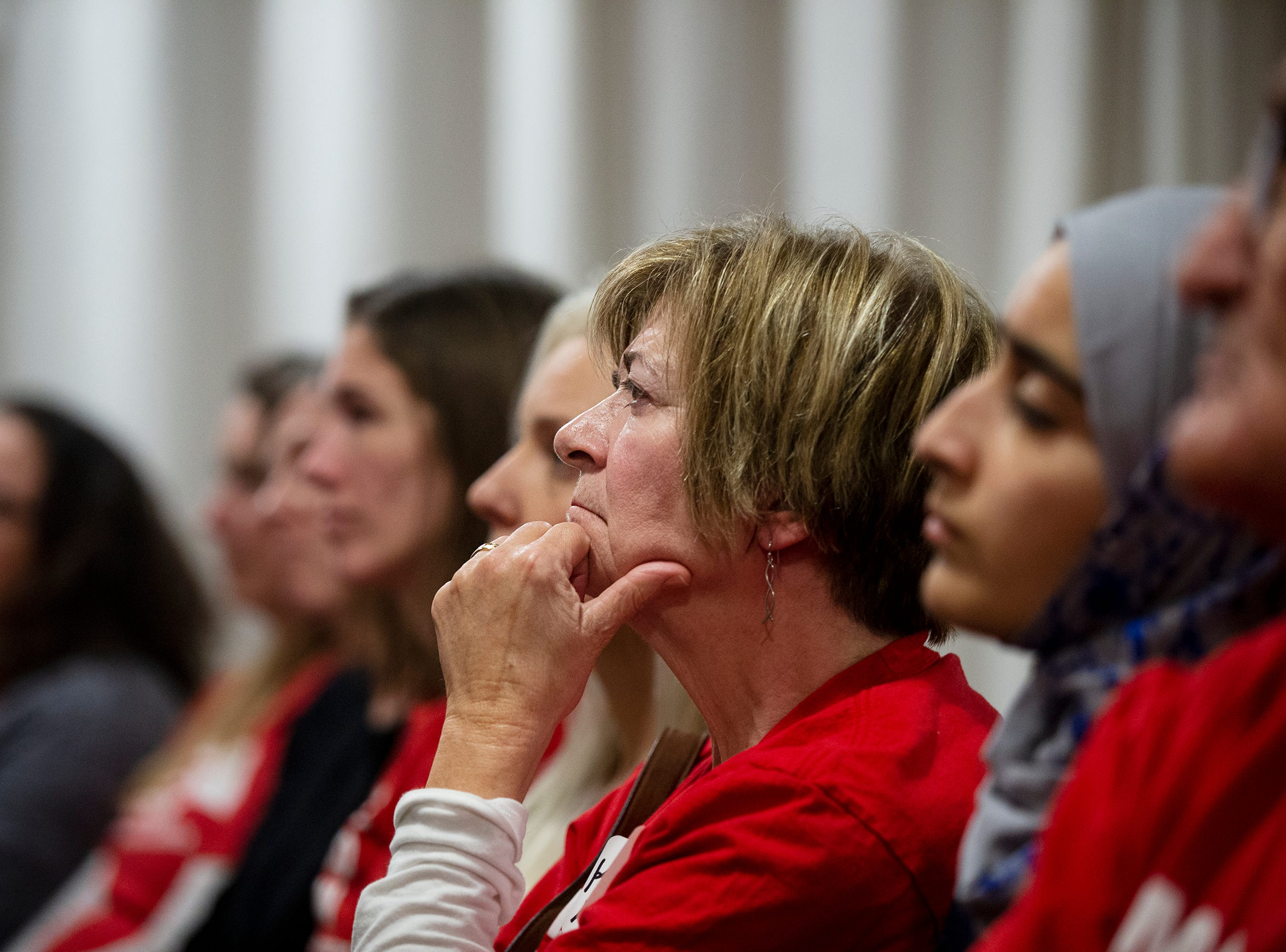 A woman listens to Former New York City Mayor Michael Bloomberg as he speaks to the crowd gathered at an Iowa Moms Demand Action member meeting on Tuesday, Dec. 4, 2018, at the Iowa Taproom in Des Moines.