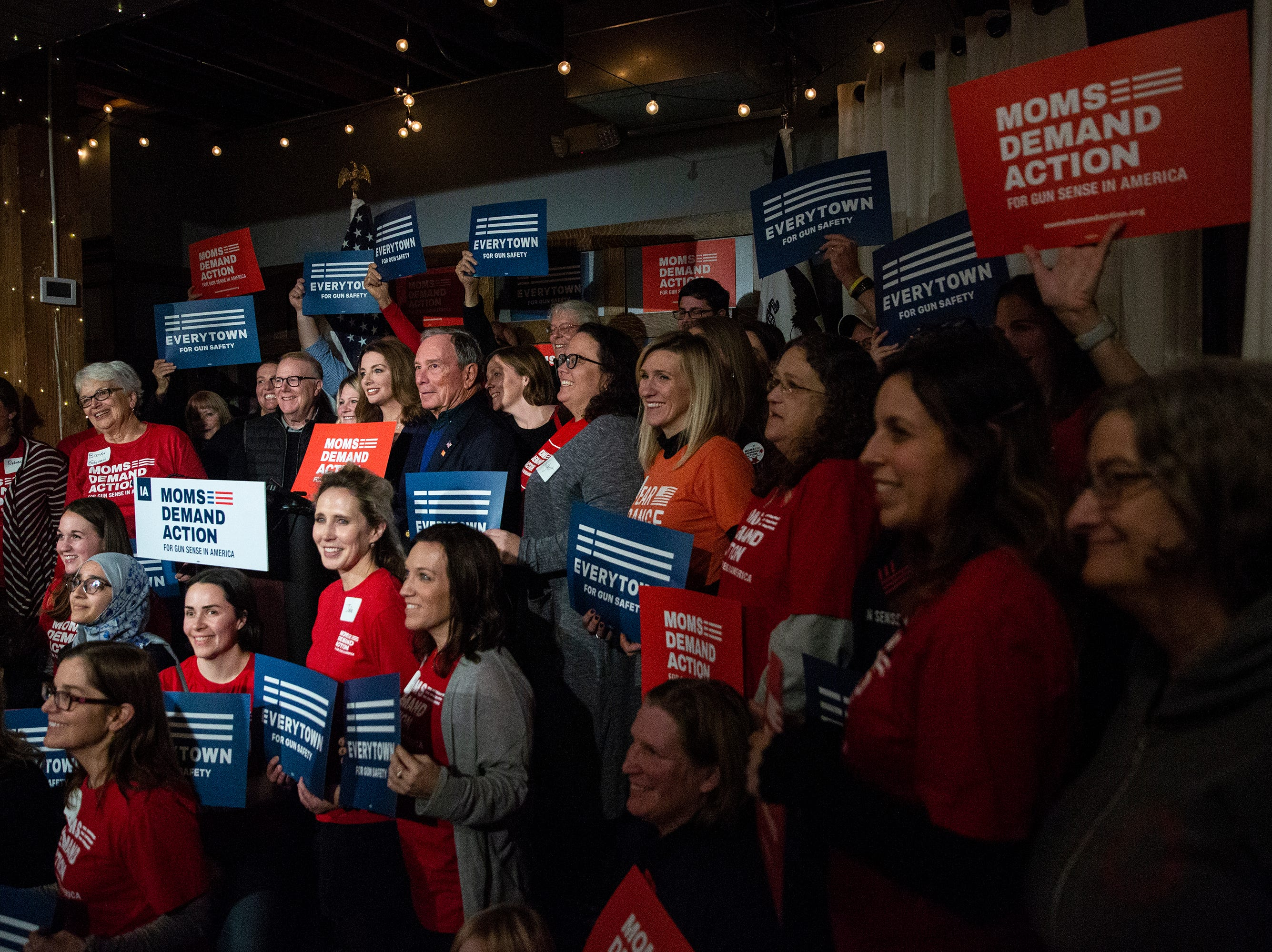 Former New York City Mayor Michael Bloomberg poses for a photo with the attendees of the Iowa Moms Demand Action member meeting he was visiting on Tuesday, Dec. 4, 2018, at the Iowa Taproom in Des Moines.