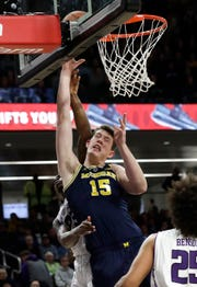 Michigan center Jon Teske shoots against Northwestern guard Jordan Ash during the first half Tuesday, Dec. 4, 2018, in Evanston, Ill.