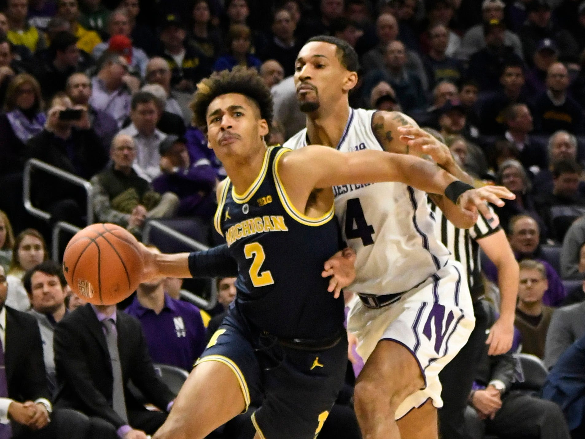 Michigan guard Jordan Poole is defended by Northwestern guard Ryan Taylor during the first half at Welsh-Ryan Arena, Dec. 4, 2018 in Evanston, Ill.