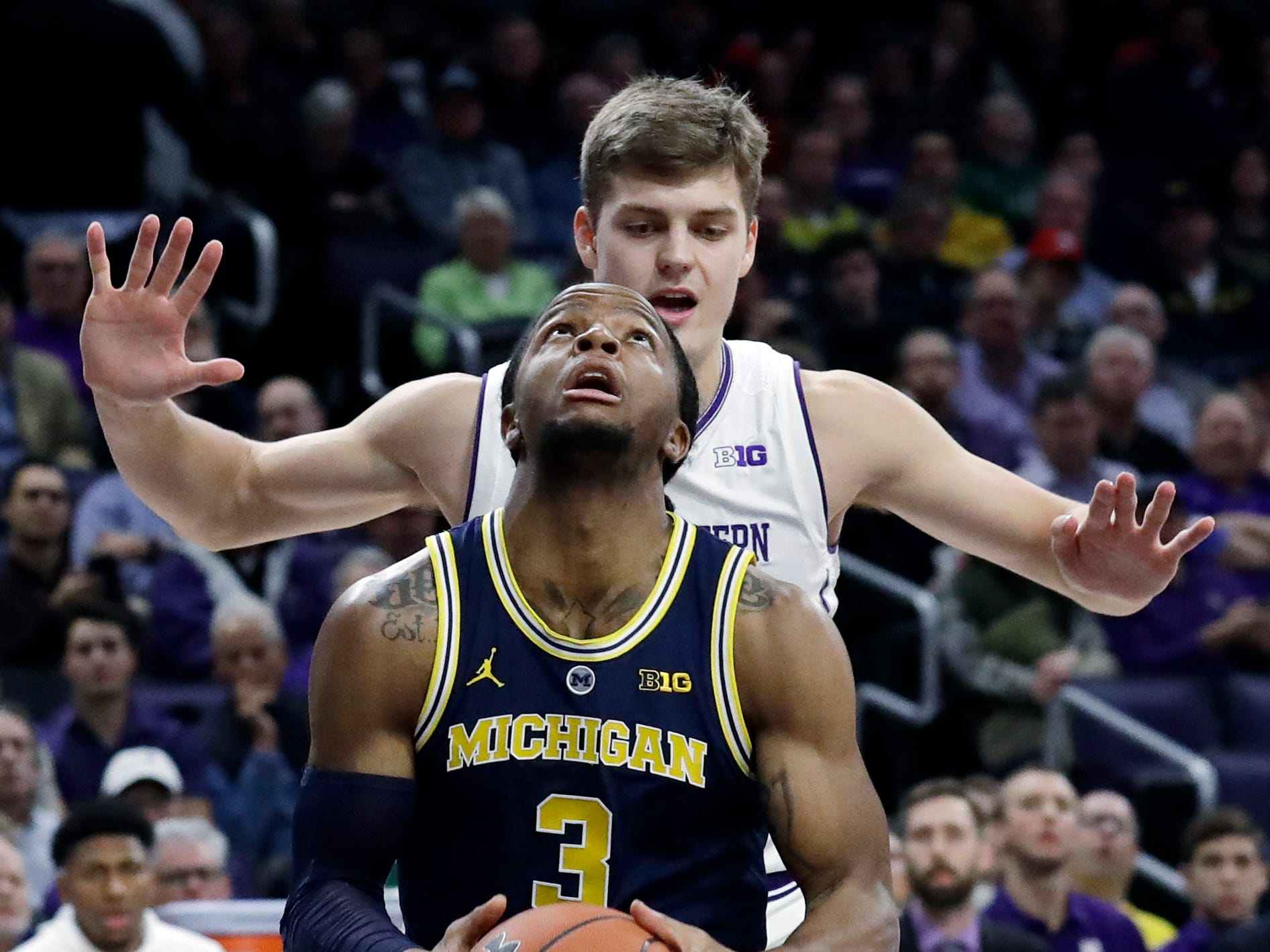 Michigan guard Zavier Simpson looks to the basket as Northwestern forward Miller Kopp guards during the first half Tuesday, Dec. 4, 2018, in Evanston, Ill.