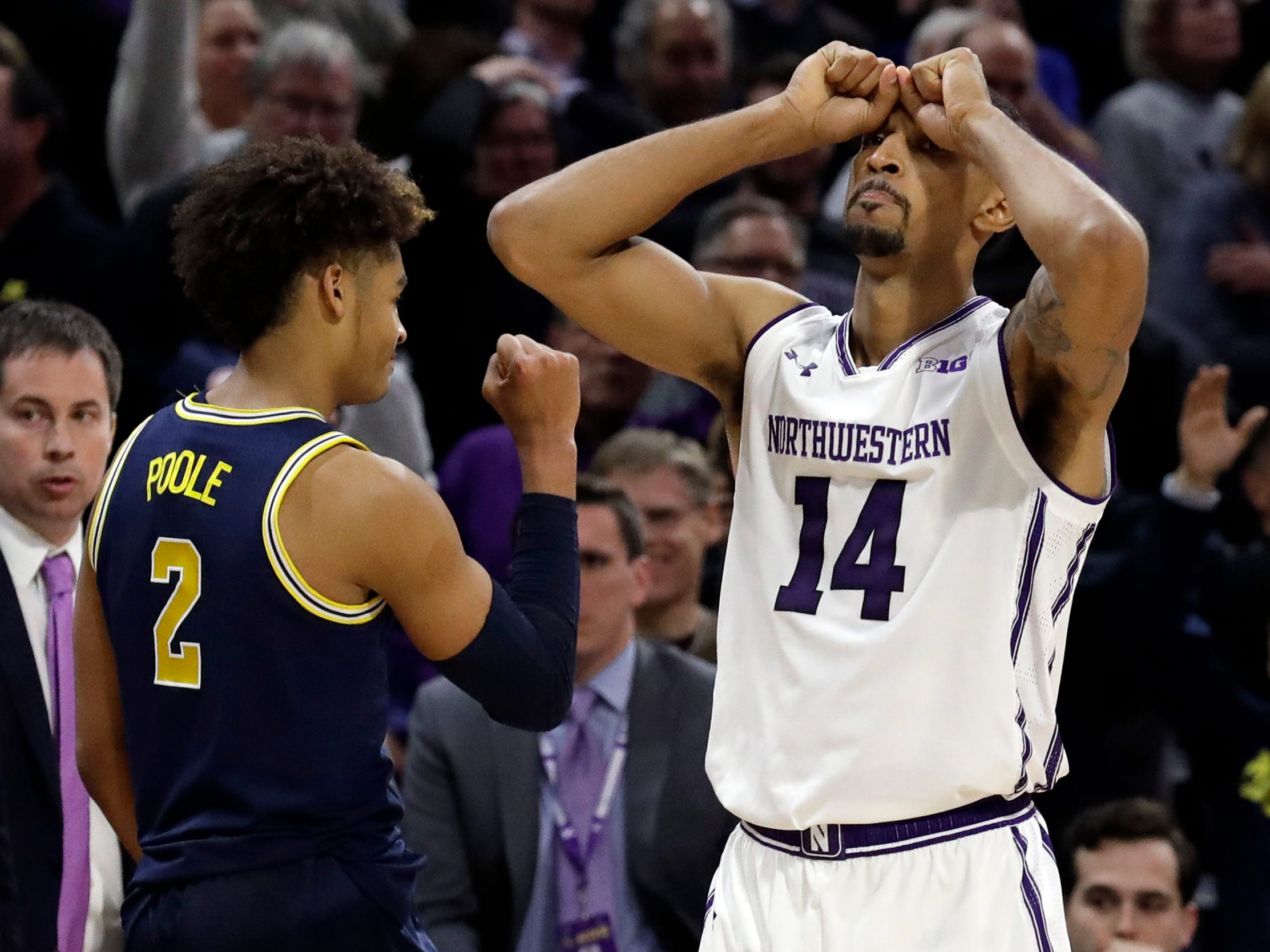 Northwestern guard Ryan Taylor reacts after missing a shot as Michigan guard Jordan Poole celebrates the 62-60 win Tuesday, Dec. 4, 2018, in Evanston, Ill.