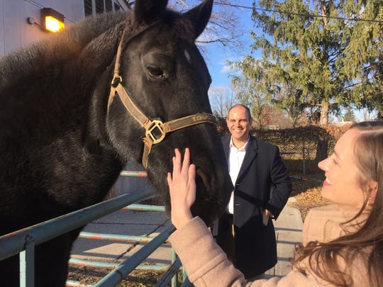 Melanie Markowicz, deputy executive of the Wayne County office of community and economic development, pets a Wayne County Sheriff's horse at Newburgh Mill, one of several old industrial mills that Wayne County hopes to convert to new destinations along Hines Drive and the Middle Rouge River. Khalil Rahal, county director of economic development, is in the background.