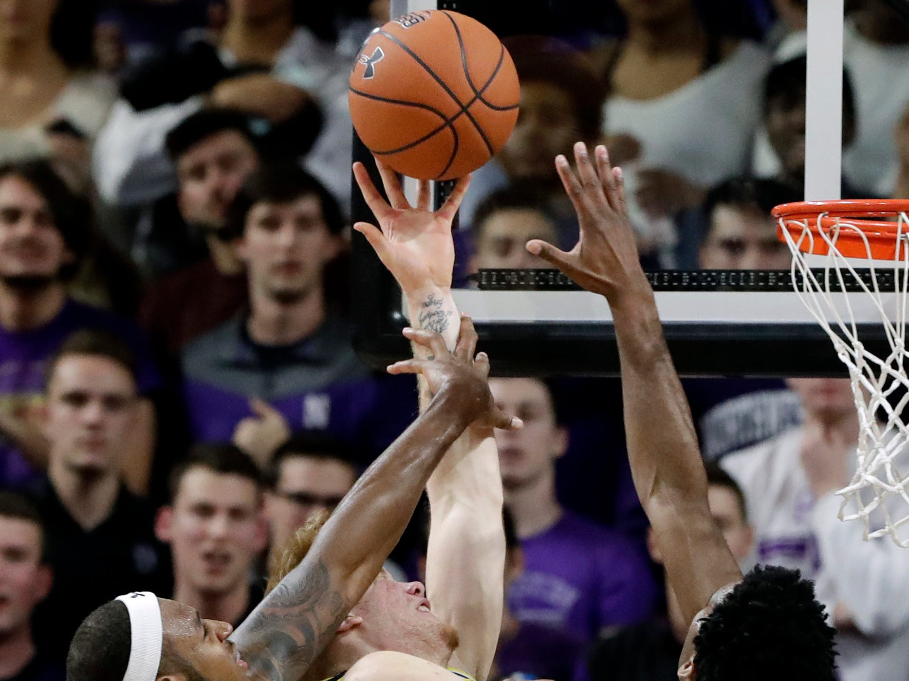 Michigan forward Ignas Brazdeikis, center, shoots against Northwestern center Dererk Pardon, left, and forward Vic Law during the second half of U-M's 62-60 win on Tuesday, Dec. 4, 2018, in Evanston, Ill.