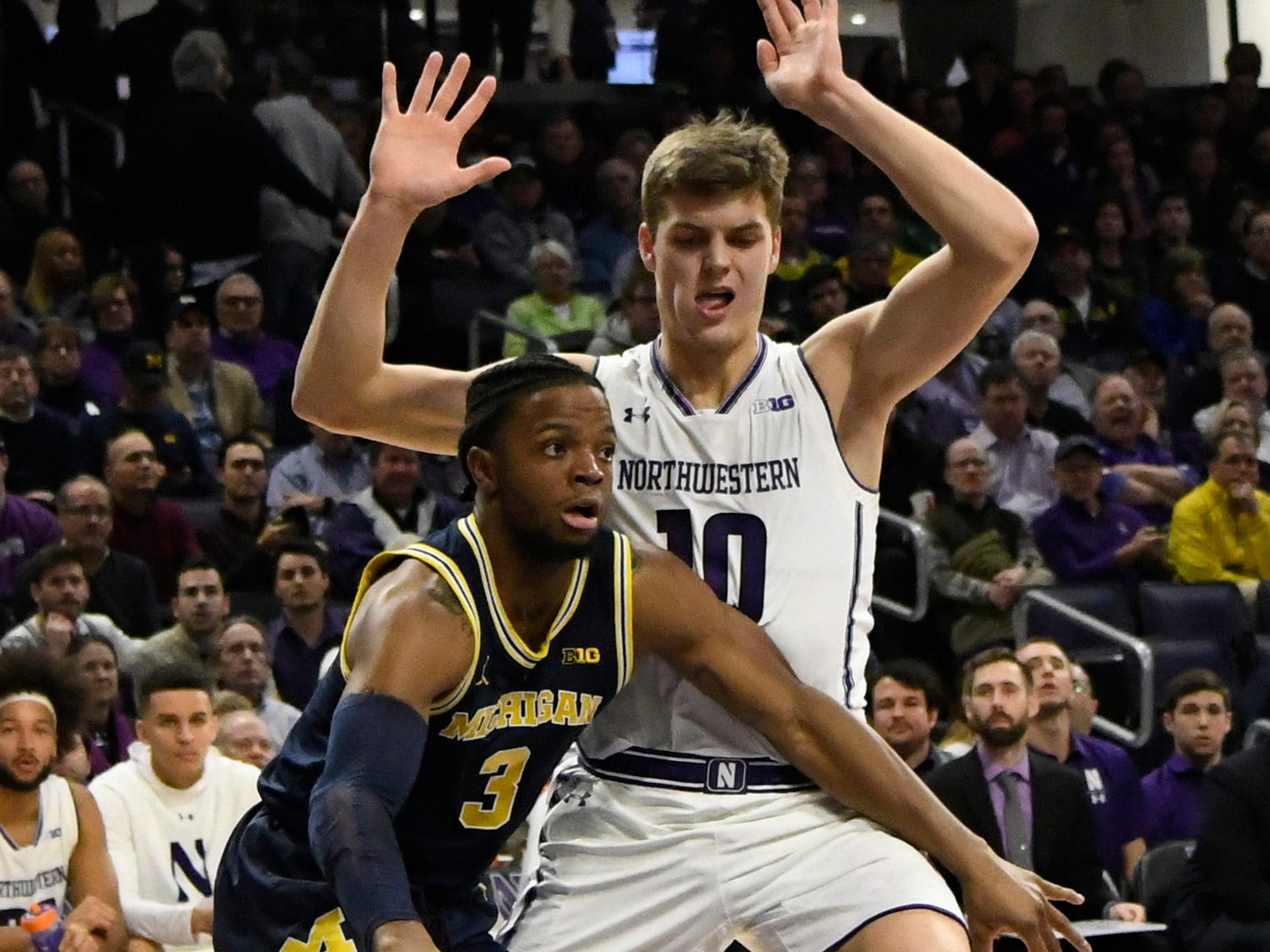 Michigan guard Zavier Simpson is defended by Northwestern forward Miller Kopp during the first half at Welsh-Ryan Arena, Dec. 4, 2018 in Evanston, Ill.